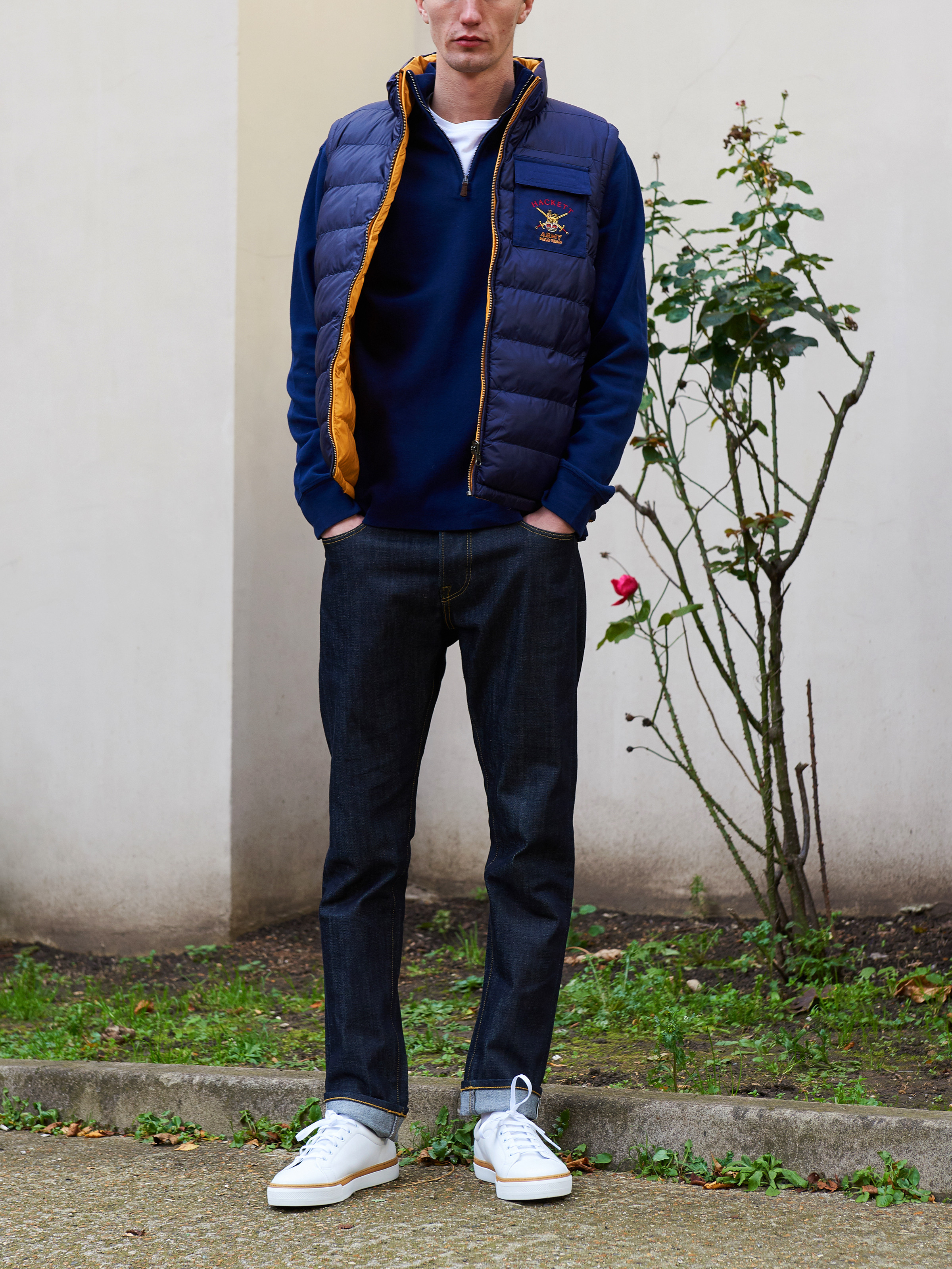 Men's outfit idea for 2021 with navy vest, half-zip / half-button sweater, white crew neck t-shirt, dark blue jeans, white sneakers. Suitable for fall and winter.
