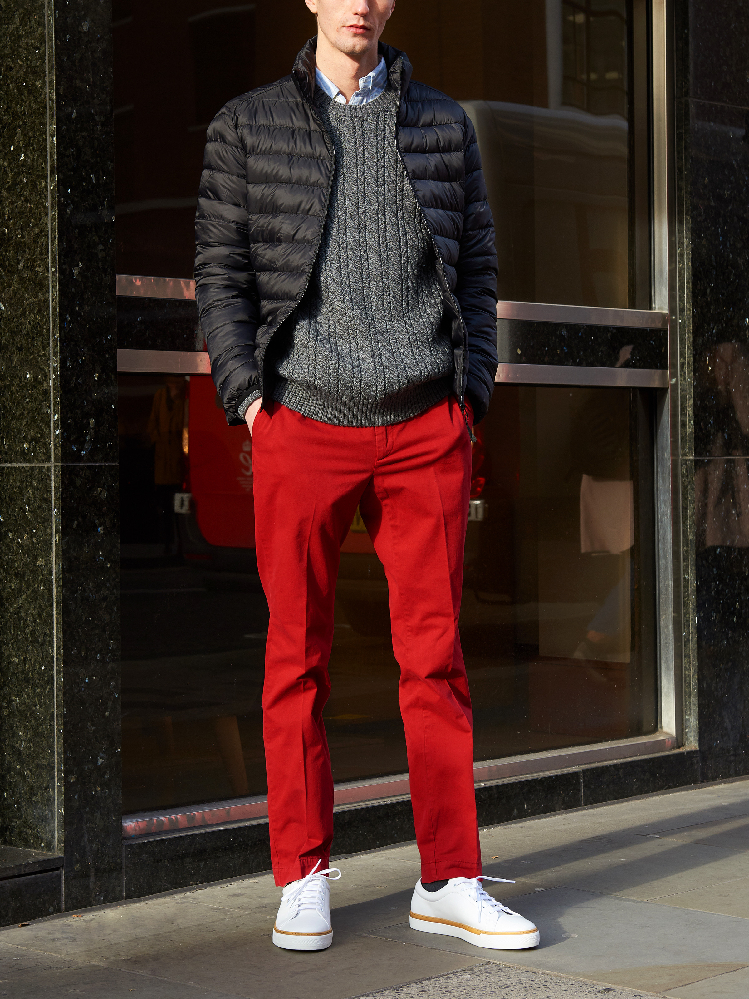 Men's outfit idea for 2021 with quilted jacket, cable-knit sweater, striped casual shirt, red chinos, white sneakers. Suitable for fall and winter.