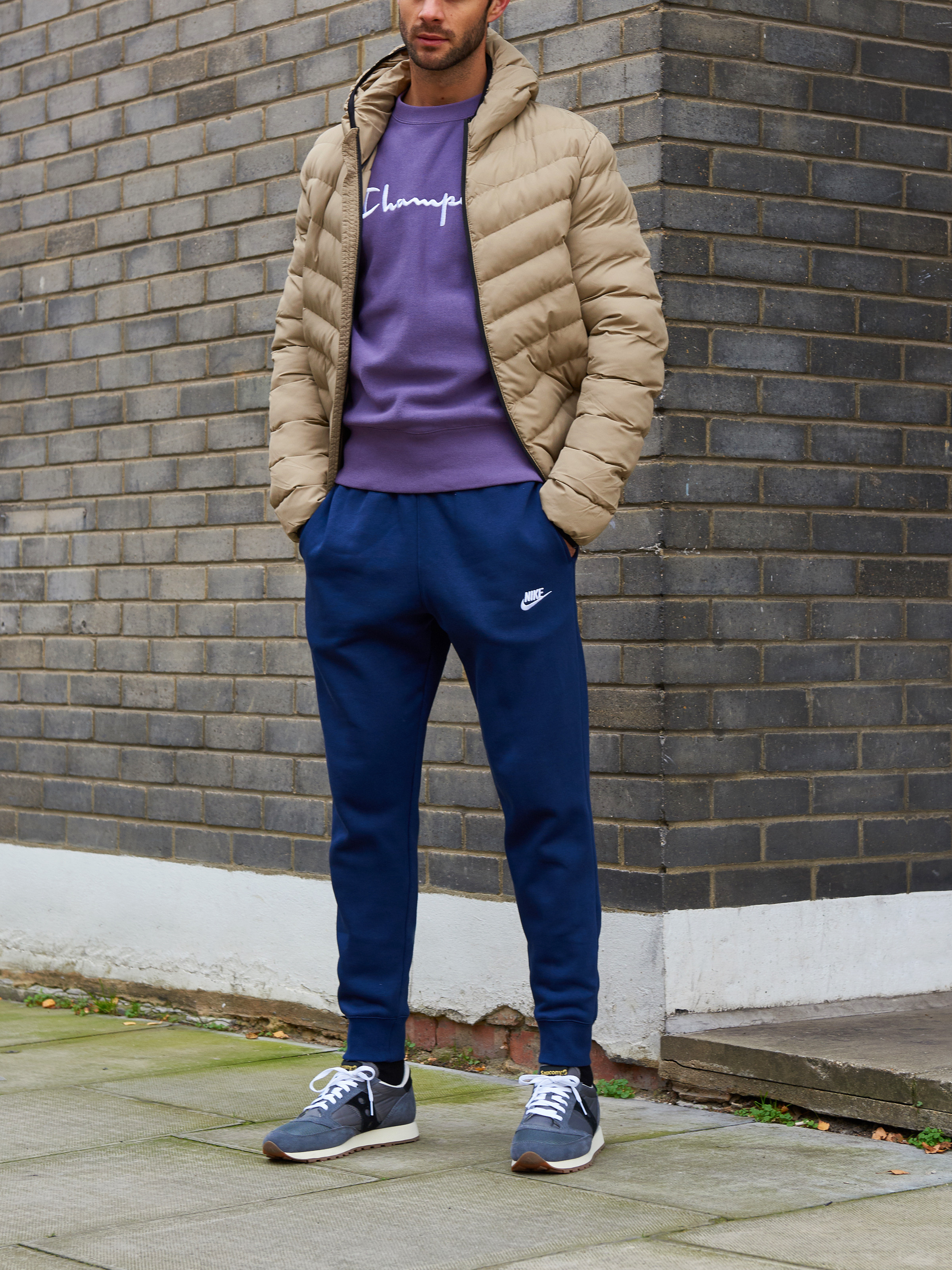 Men's outfit idea for 2021 with brown down coat, purple logo / printed sweatshirt, sweatpants, neutral sneakers. Suitable for fall and winter.