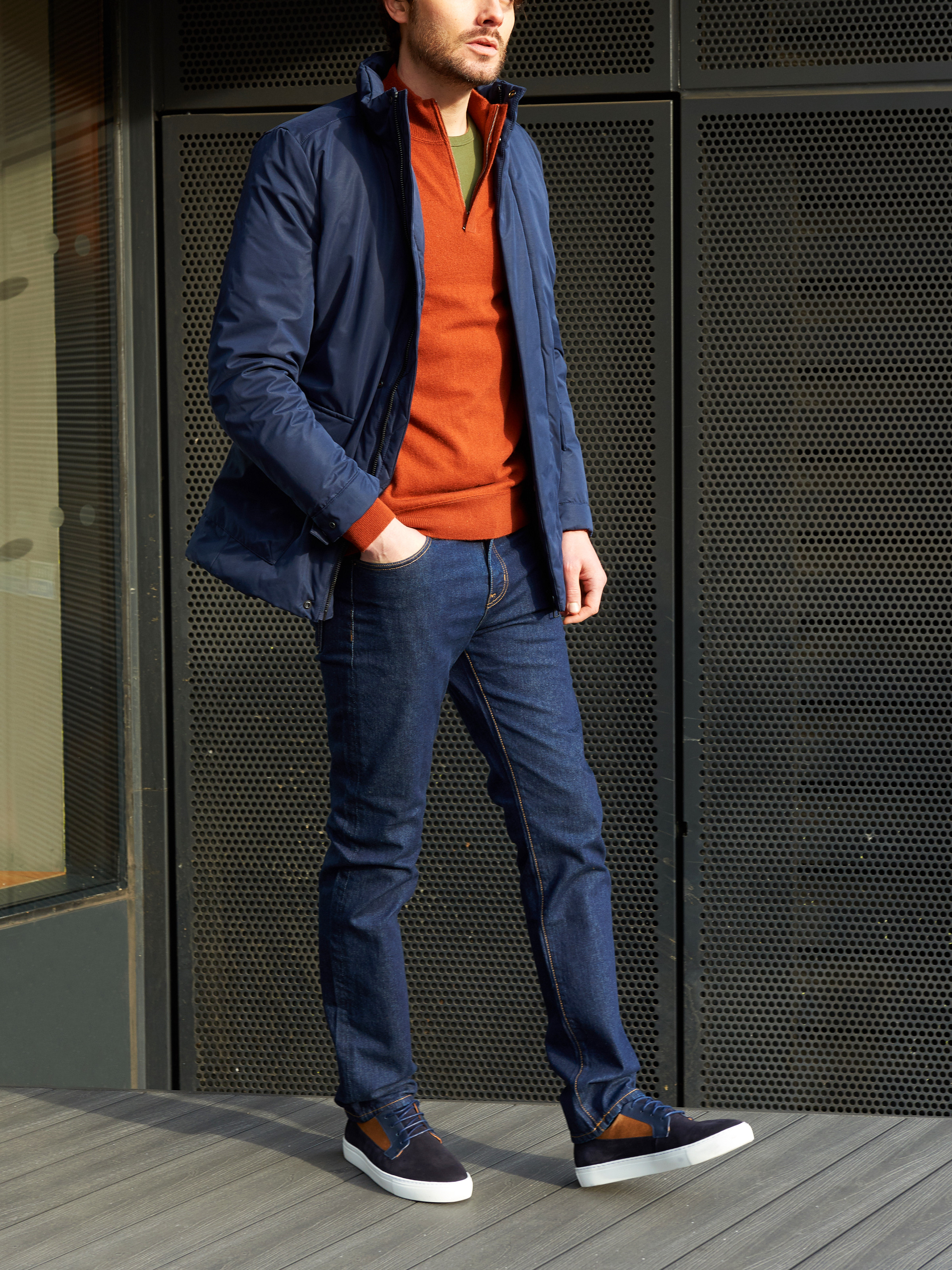 Men's outfit idea for 2021 with waterproof jacket / windbreaker, half-zip / half-button sweater, bold-colored crew neck t-shirt, dark blue jeans, neutral sneakers. Suitable for fall and winter.
