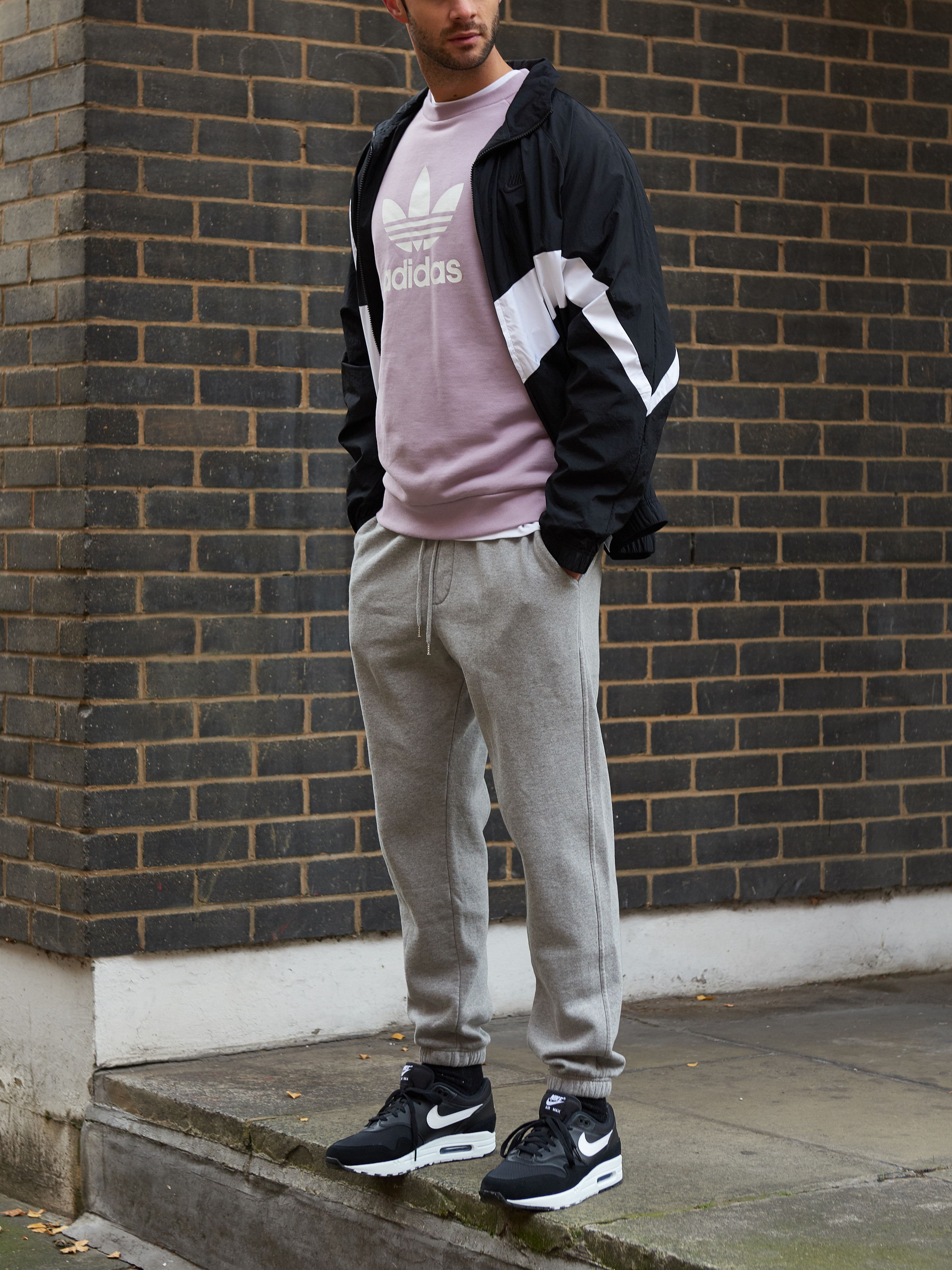 Men's outfit idea for 2021 with varsity / track jacket, purple logo / printed sweatshirt, sweatpants, black sneakers. Suitable for fall and winter.