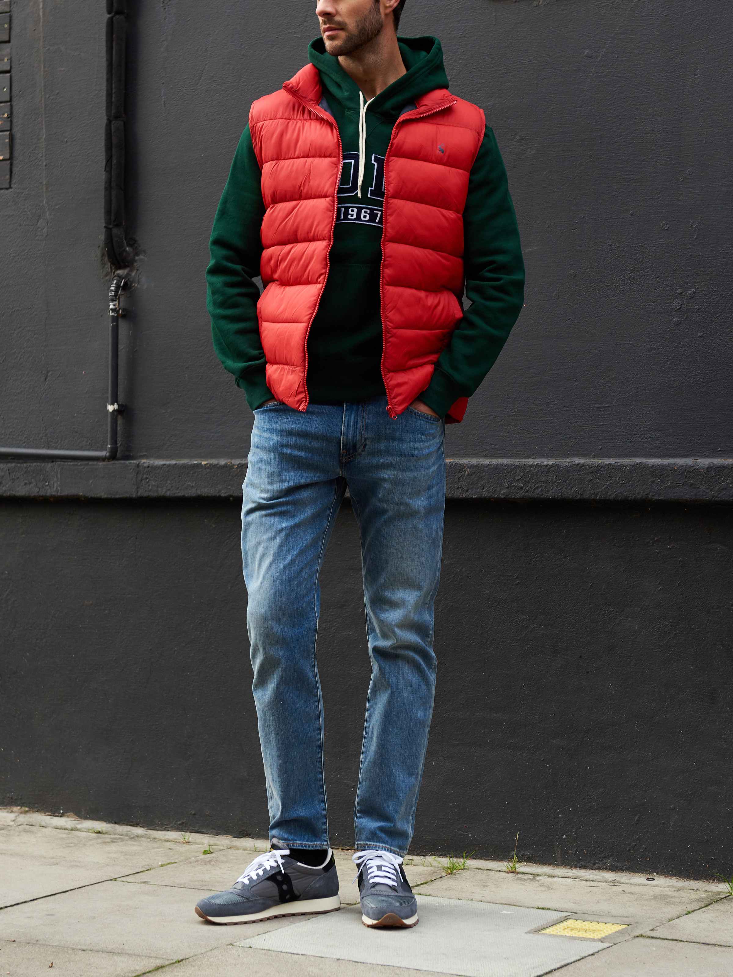 Men's outfit idea for 2021 with red vest, logo / printed hoodie, light blue jeans, neutral sneakers. Suitable for fall and winter.