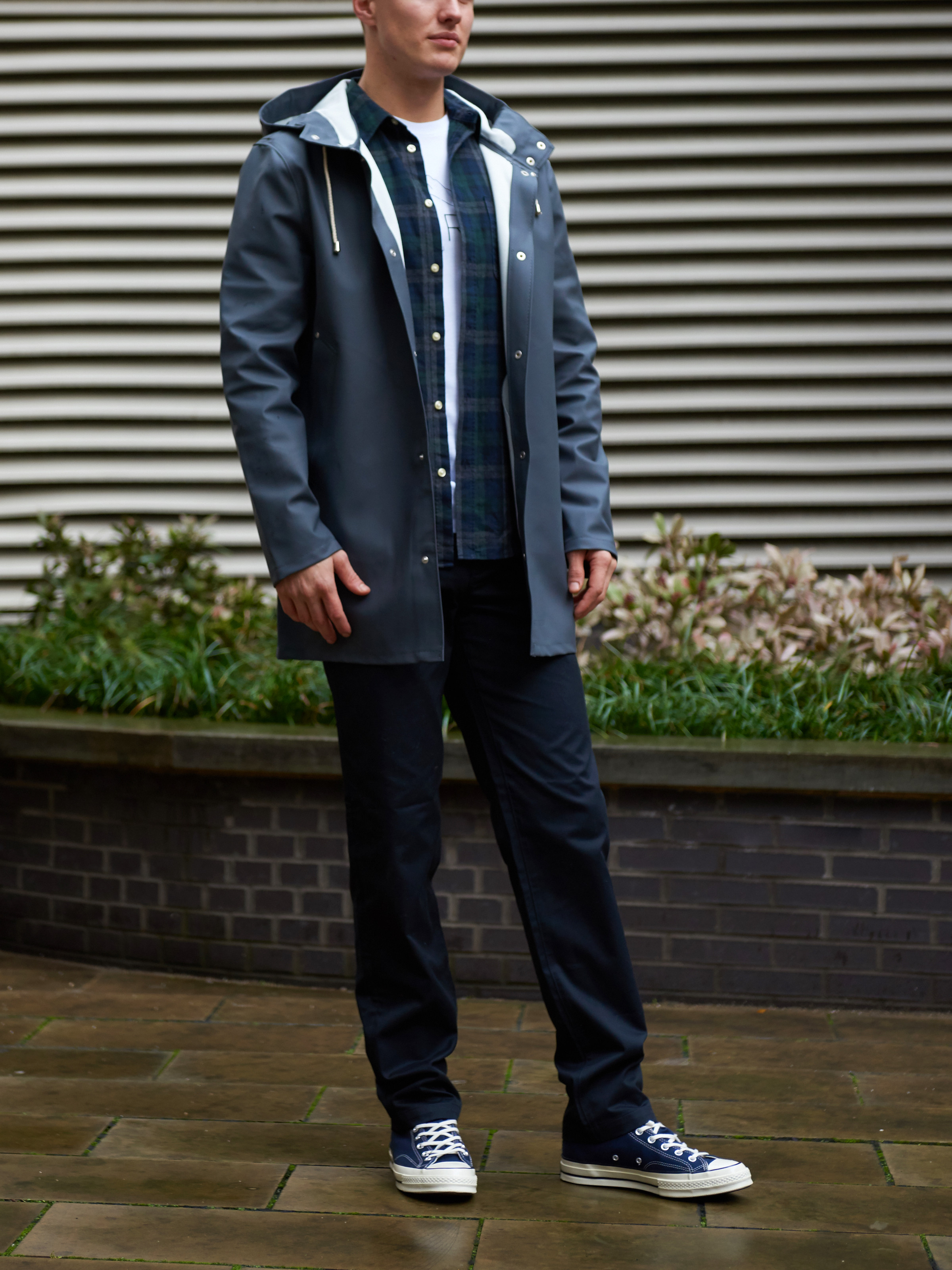 Men's outfit idea for 2021 with navy raincoat, neutral plaid shirt, graphic printed crew neck t-shirt, navy chinos, converse. Suitable for spring, fall and winter.