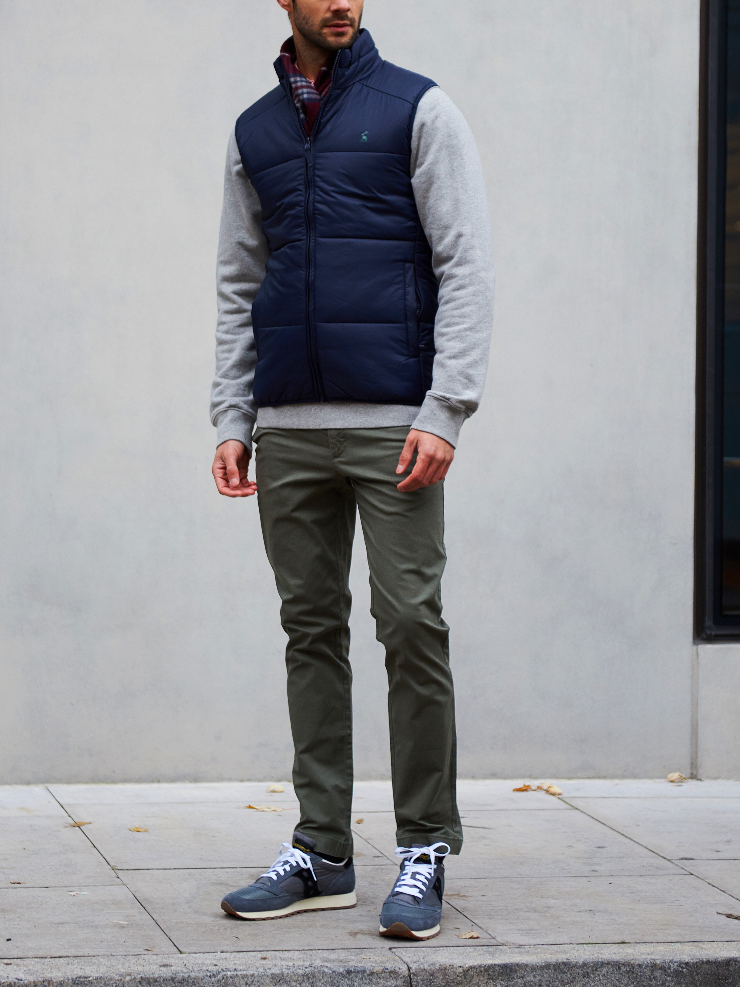 Men's outfit idea for 2021 with vest, gray sweatshirt, colored chinos, neutral sneakers. Suitable for fall and winter.