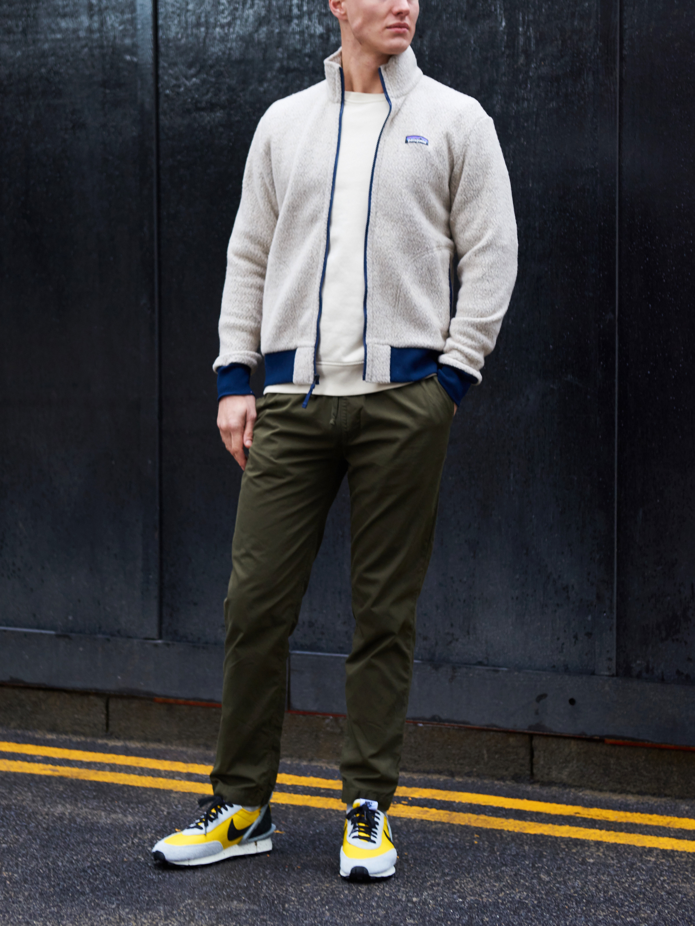 Men's outfit idea for 2021 with neutral wool jacket, bold-colored sweatshirt, colored chinos, bright sneakers. Suitable for fall and winter.
