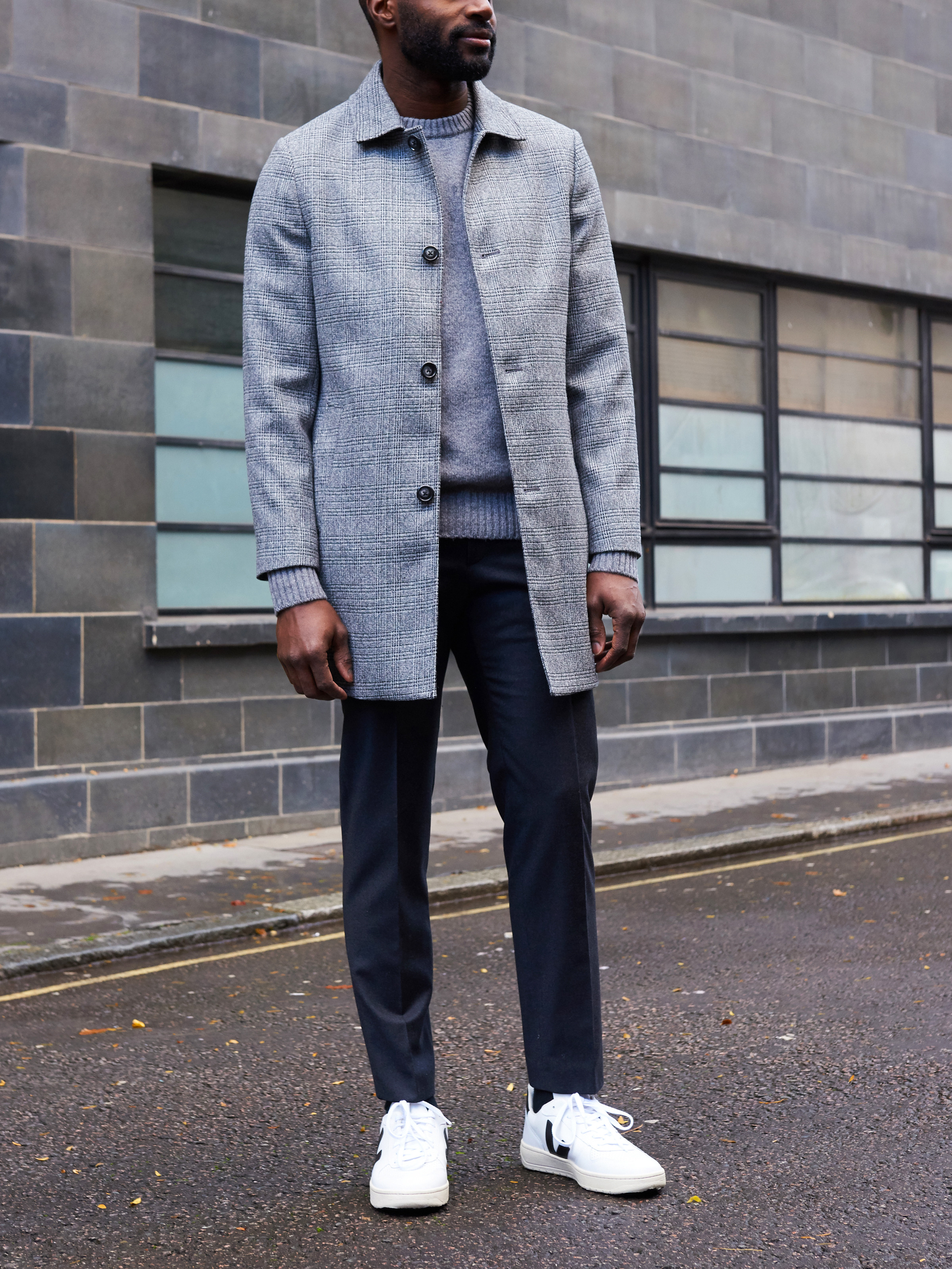 Men's outfit idea for 2021 with grey single-breasted overcoat, gray crew neck knitted sweater, navy dress pants, white sneakers. Suitable for fall and winter.