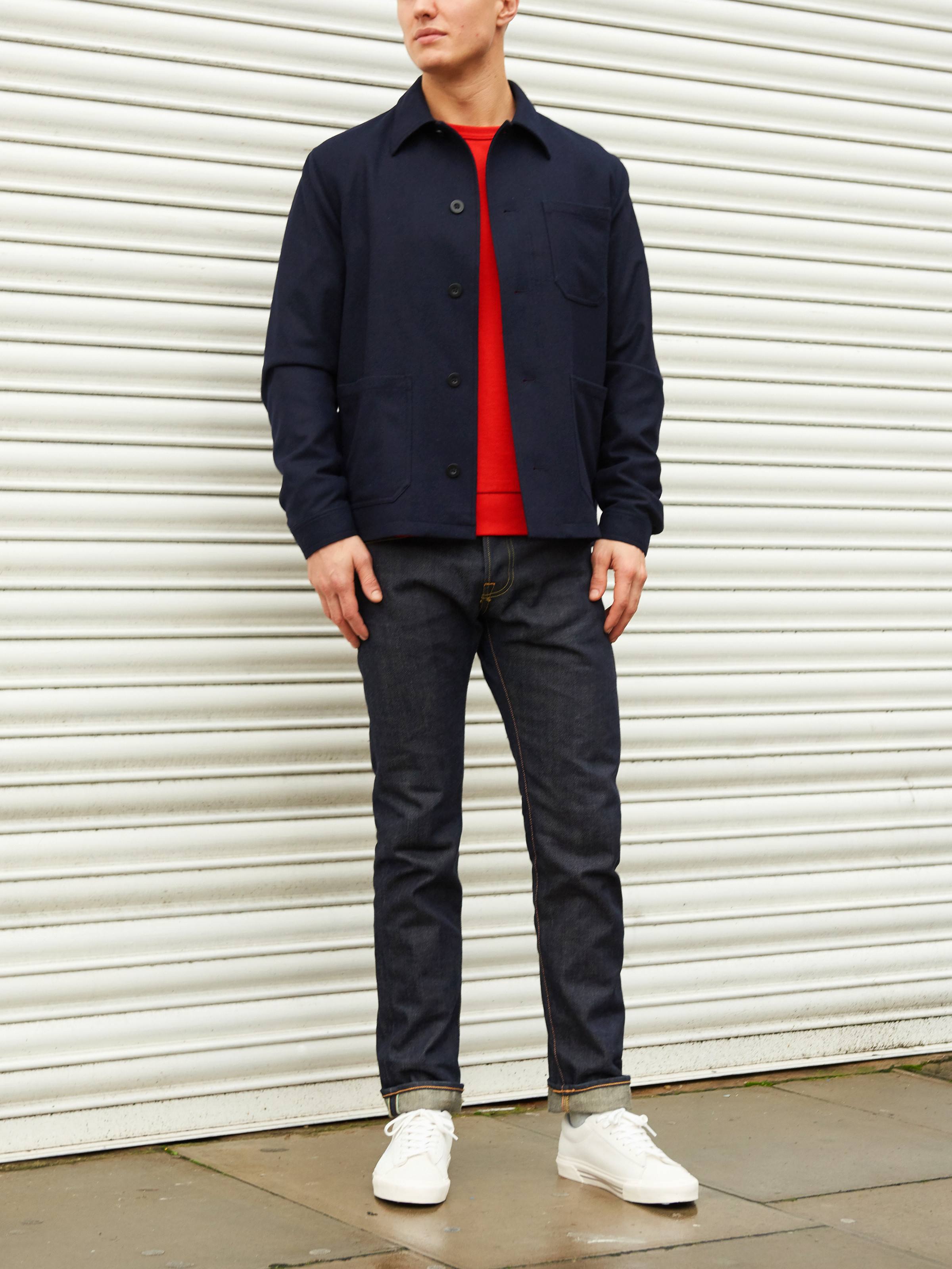 Men's outfit idea for 2021 with utility jacket, bold-colored sweatshirt, dark blue jeans, white sneakers. Suitable for spring and fall.