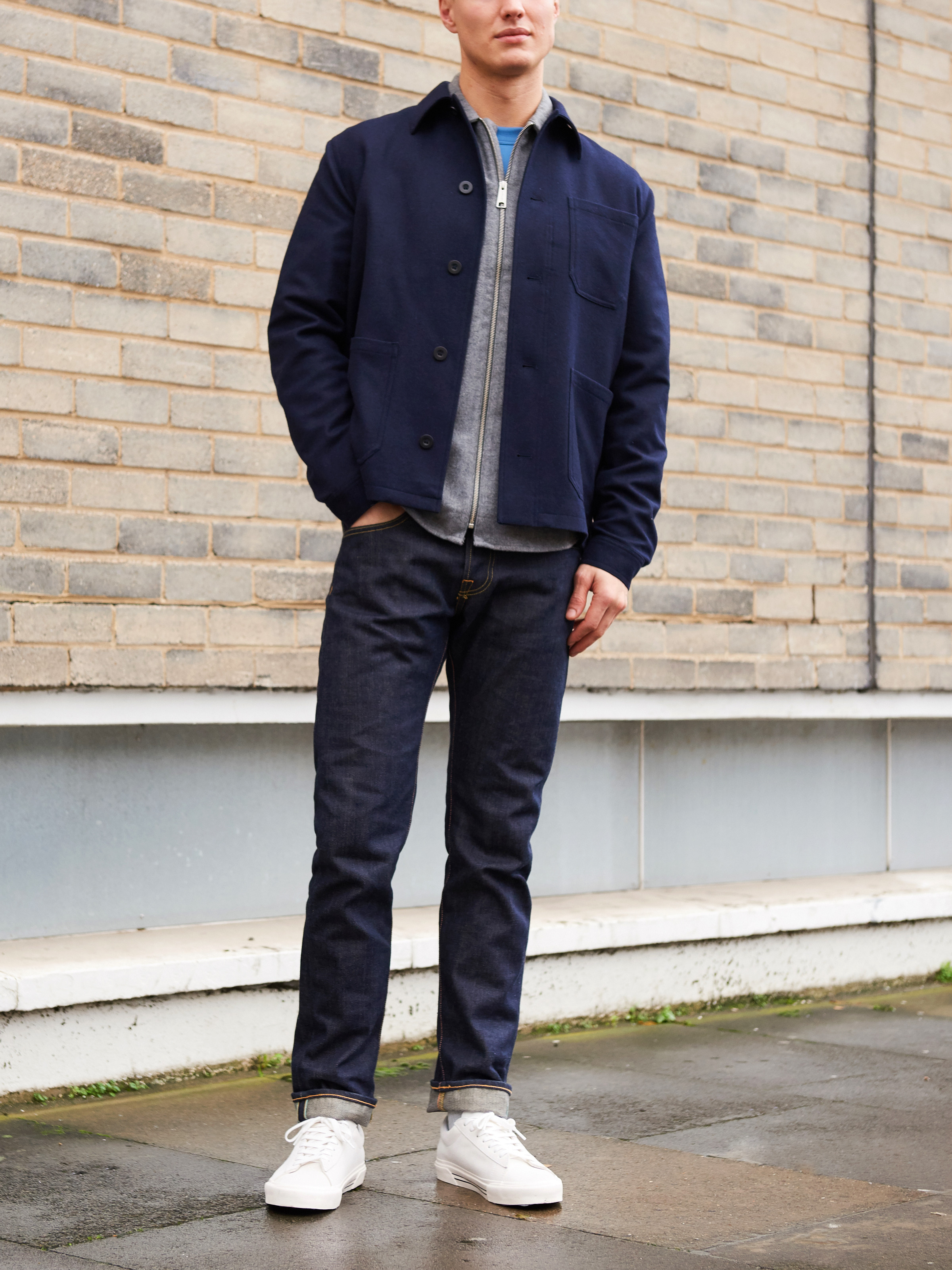 Men's outfit idea for 2021 with utility jacket, grey overshirt, bold-colored crew neck t-shirt, dark blue jeans, white sneakers. Suitable for fall and winter.