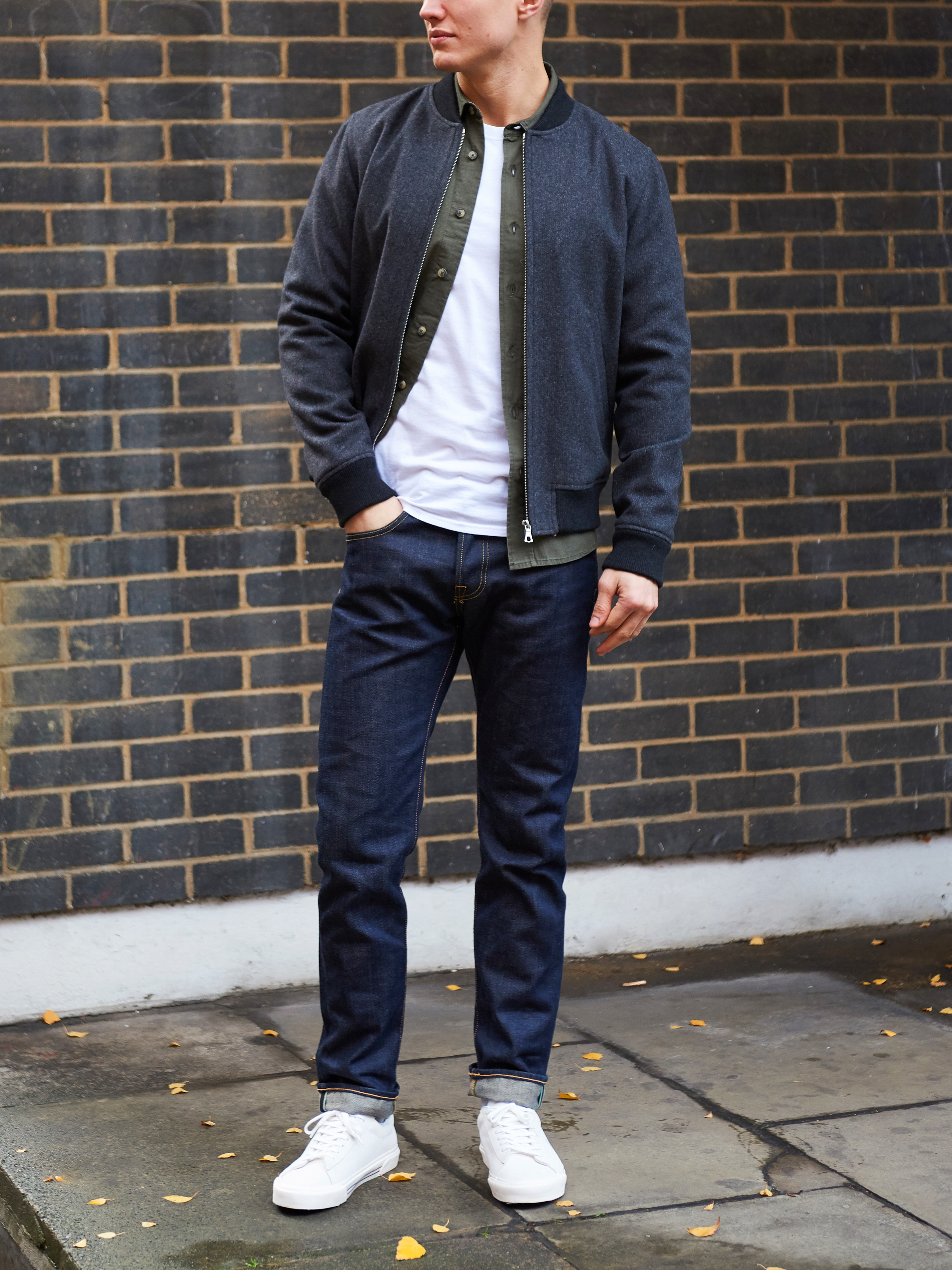 Men's outfit idea for 2021 with bomber jacket, overshirt, white crew neck t-shirt, dark blue jeans, white sneakers. Suitable for fall and winter.