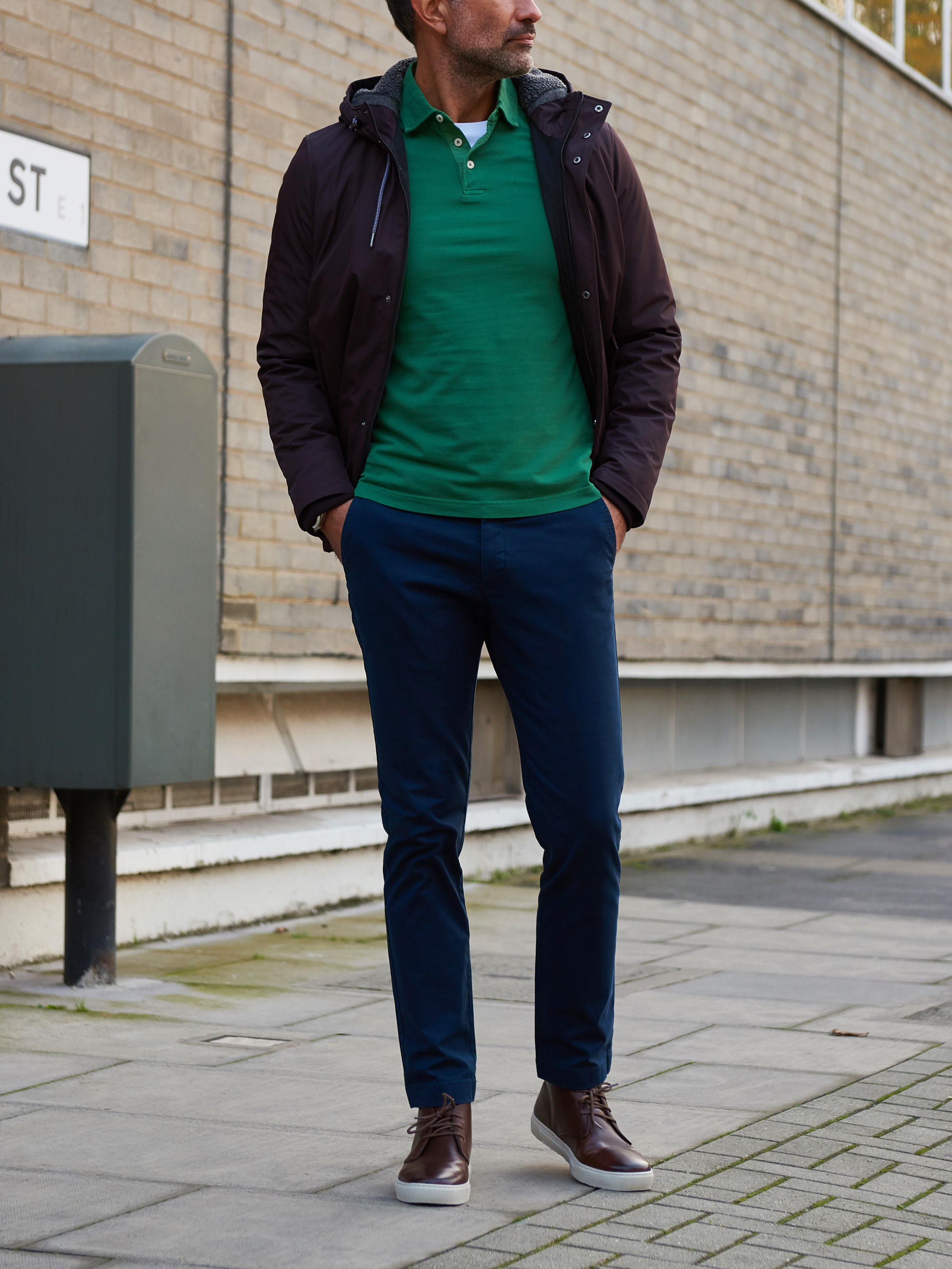 Men's outfit idea for 2021 with waterproof jacket / windbreaker, green long-sleeved polo, navy chinos, chukka boots. Suitable for fall and winter.