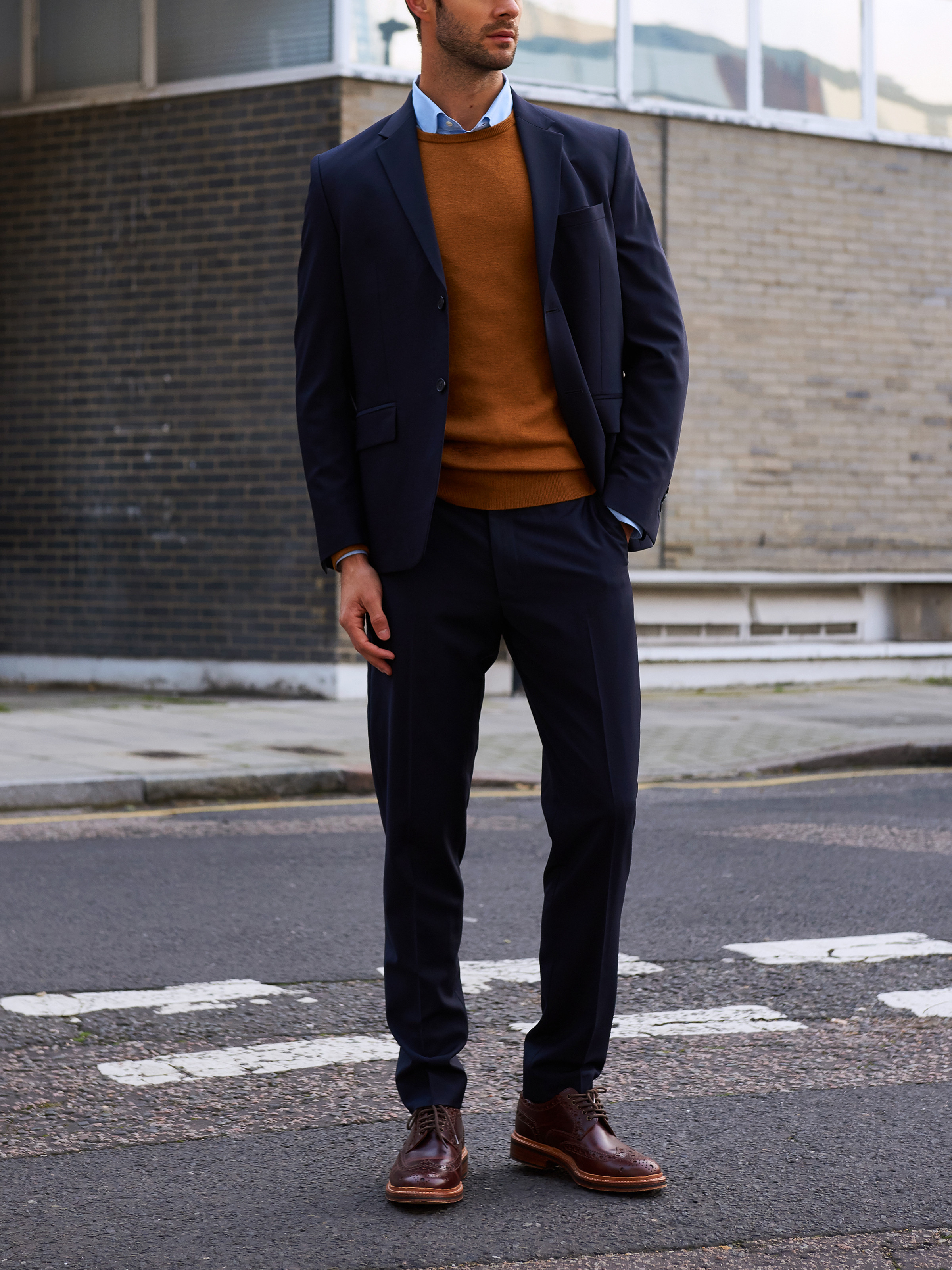 Men's outfit idea for 2021 with navy plain blazer, bold-colored crew neck sweater, blue dress shirt, navy plain dress pants, brown brogues. Suitable for fall and winter.