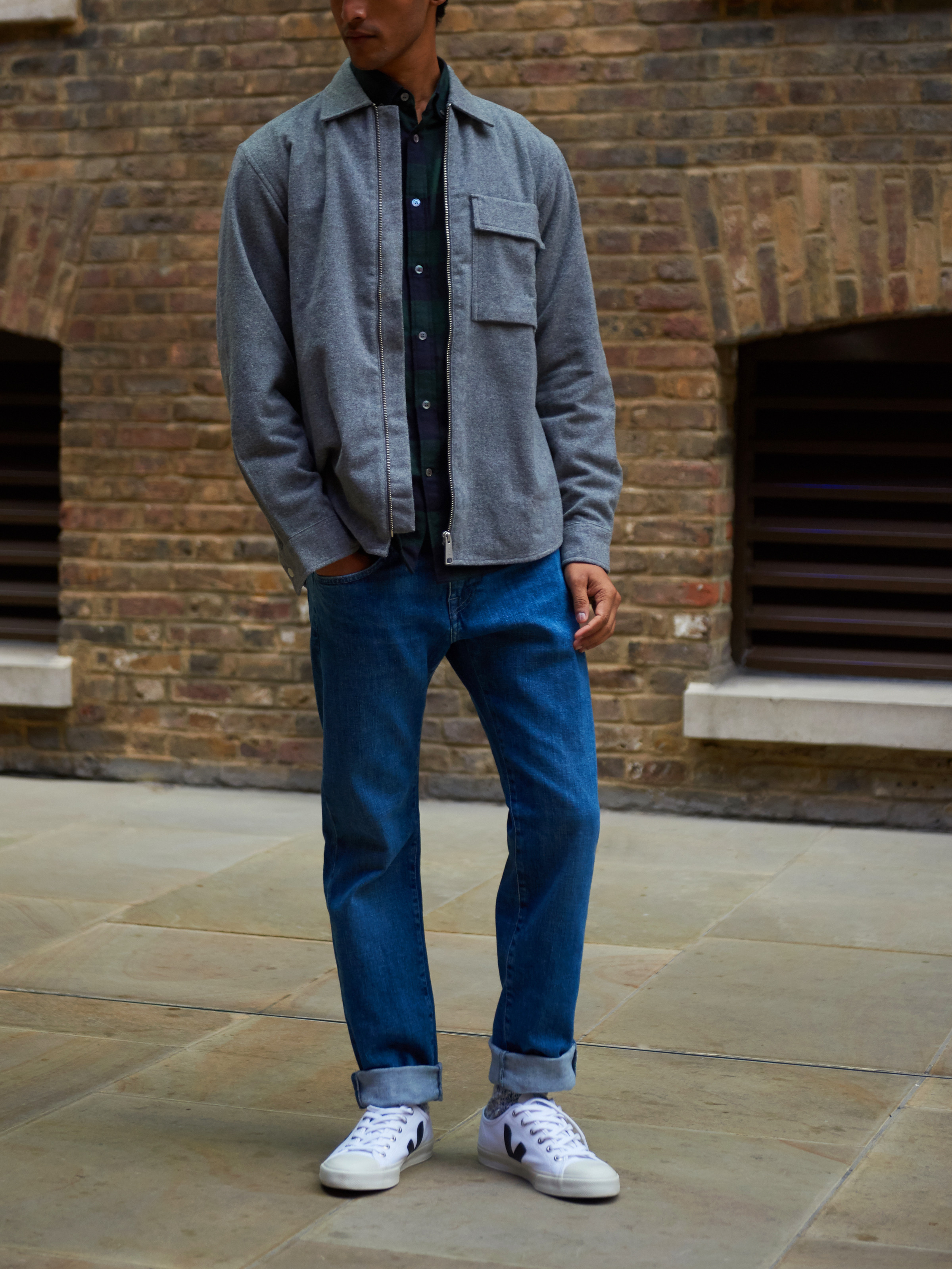 Men's outfit idea for 2021 with overshirt, bold plaid shirt, mid blue jeans, white sneakers. Suitable for spring, fall and winter.