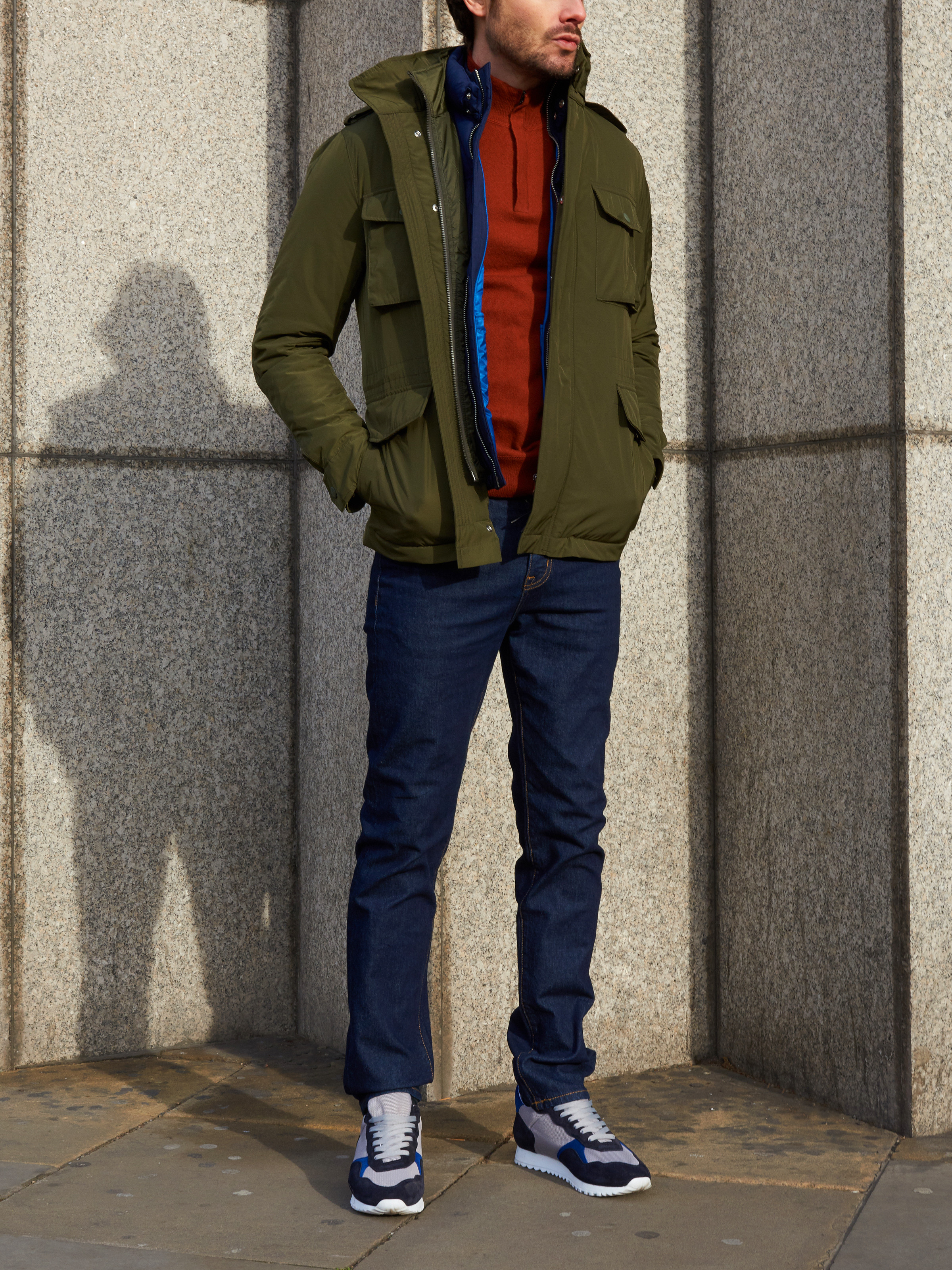 Men's outfit idea for 2021 with field jacket, half-zip / half-button sweater, dark blue jeans, neutral sneakers. Suitable for fall and winter.