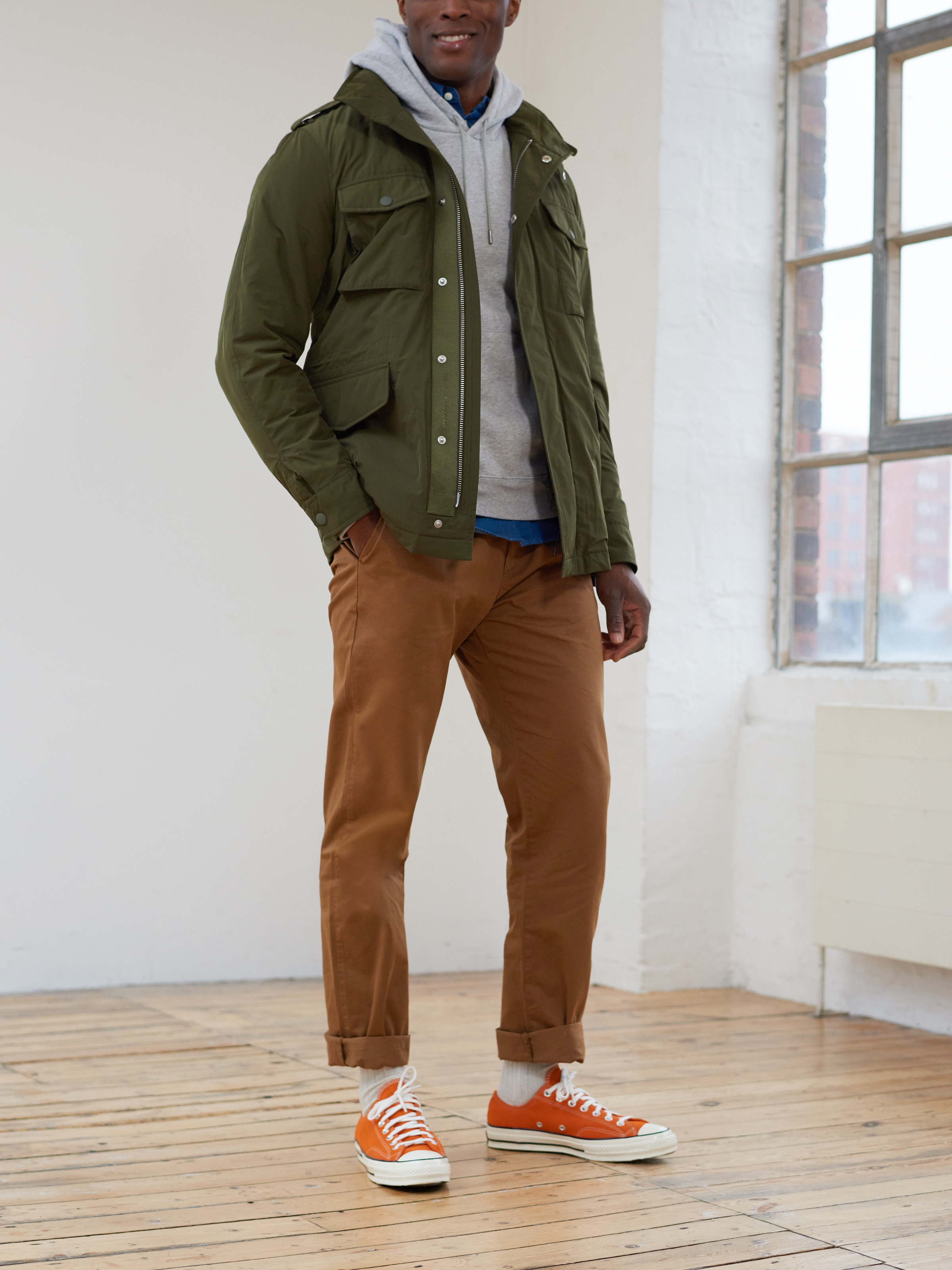 Men's outfit idea for 2021 with green field jacket, gray hoodie, denim shirt, brown chinos. Suitable for fall and winter.
