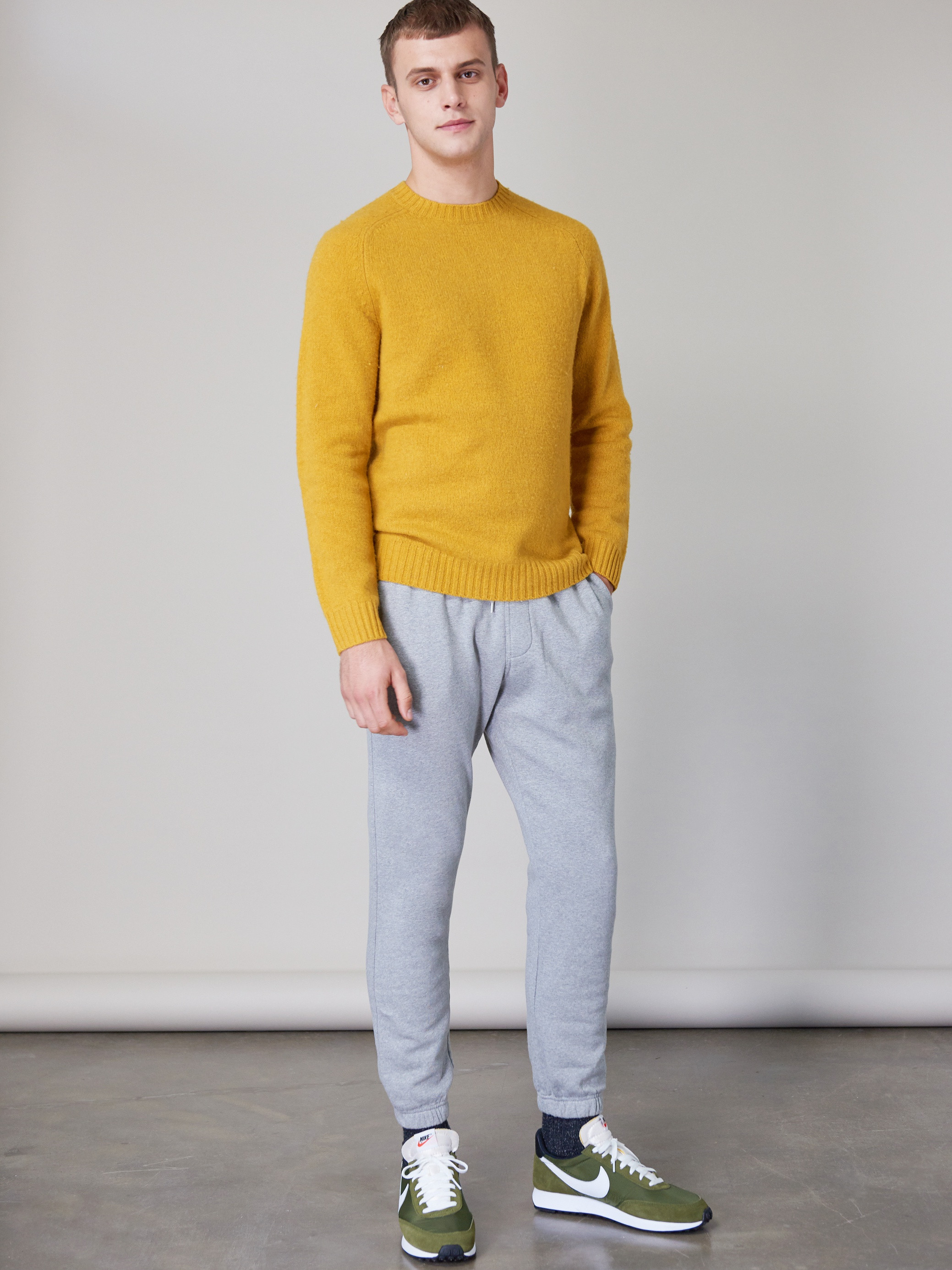 Men's outfit idea for 2021 with yellow plain crew neck knitted sweater, sweatpants, neutral sneakers. Suitable for spring, fall and winter.
