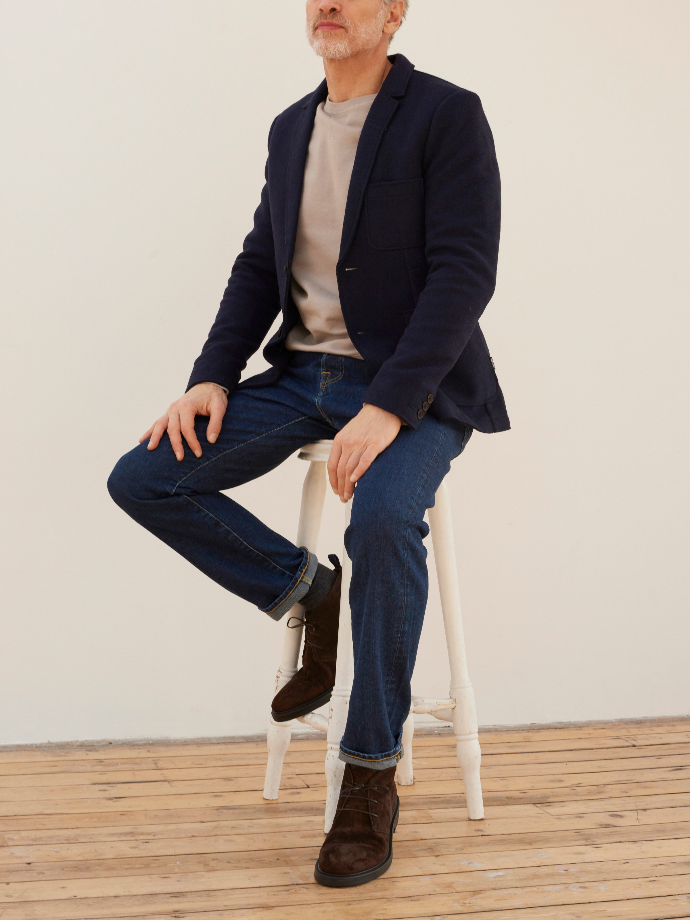 Men's outfit idea for 2021 with textured blazer, bold coloured sweatshirt, dark blue jeans, brown desert boots. Suitable for spring and autumn.