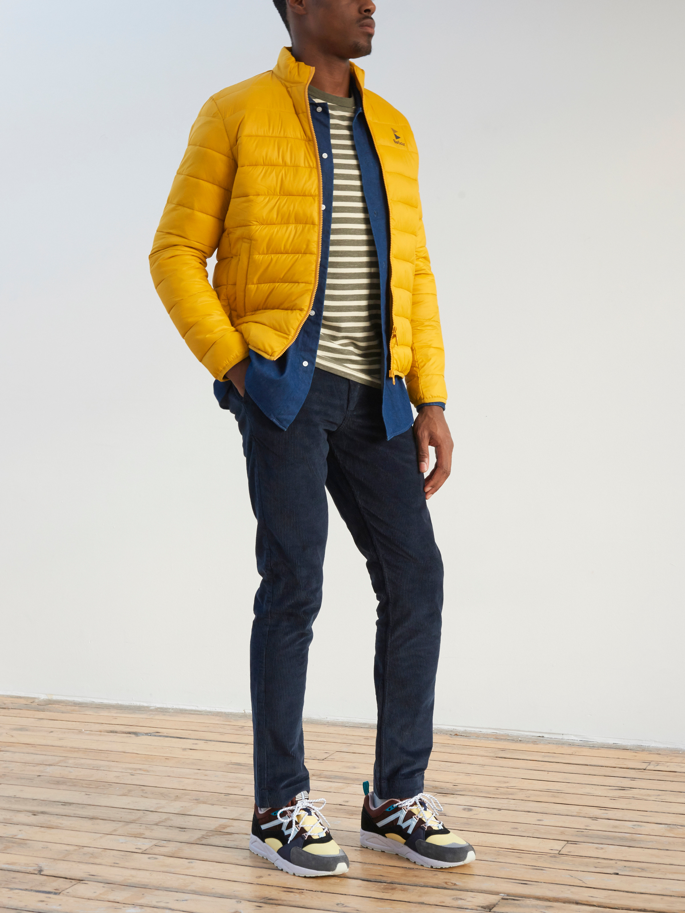 Men's outfit idea for 2021 with yellow quilted jacket, denim shirt, striped crew neck t-shirt, corduroy pants, neutral sneakers. Suitable for spring, fall and winter.