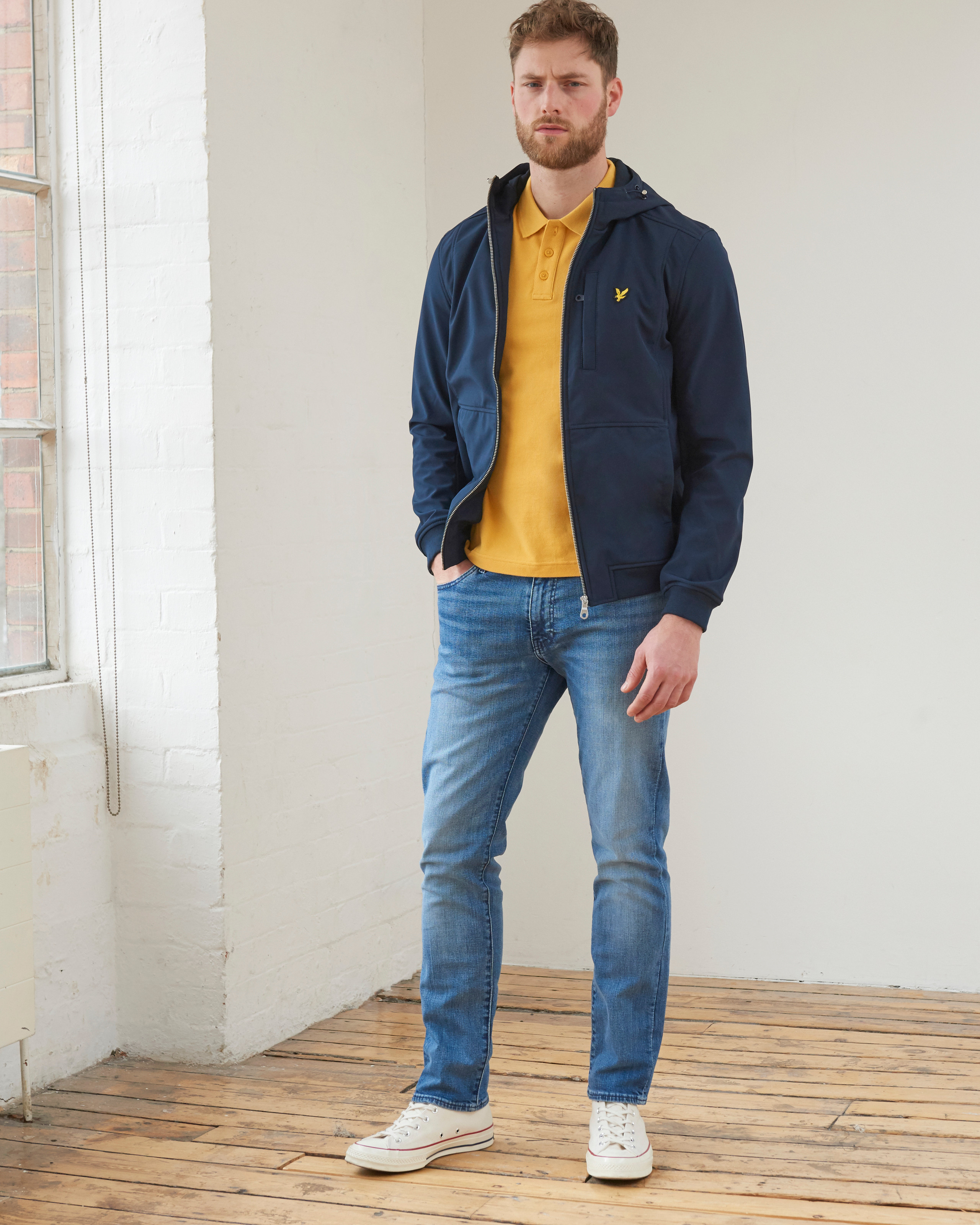 Men's outfit idea for 2021 with waterproof jacket / windbreaker, bold coloured polo, mid blue jeans. Suitable for spring and autumn.