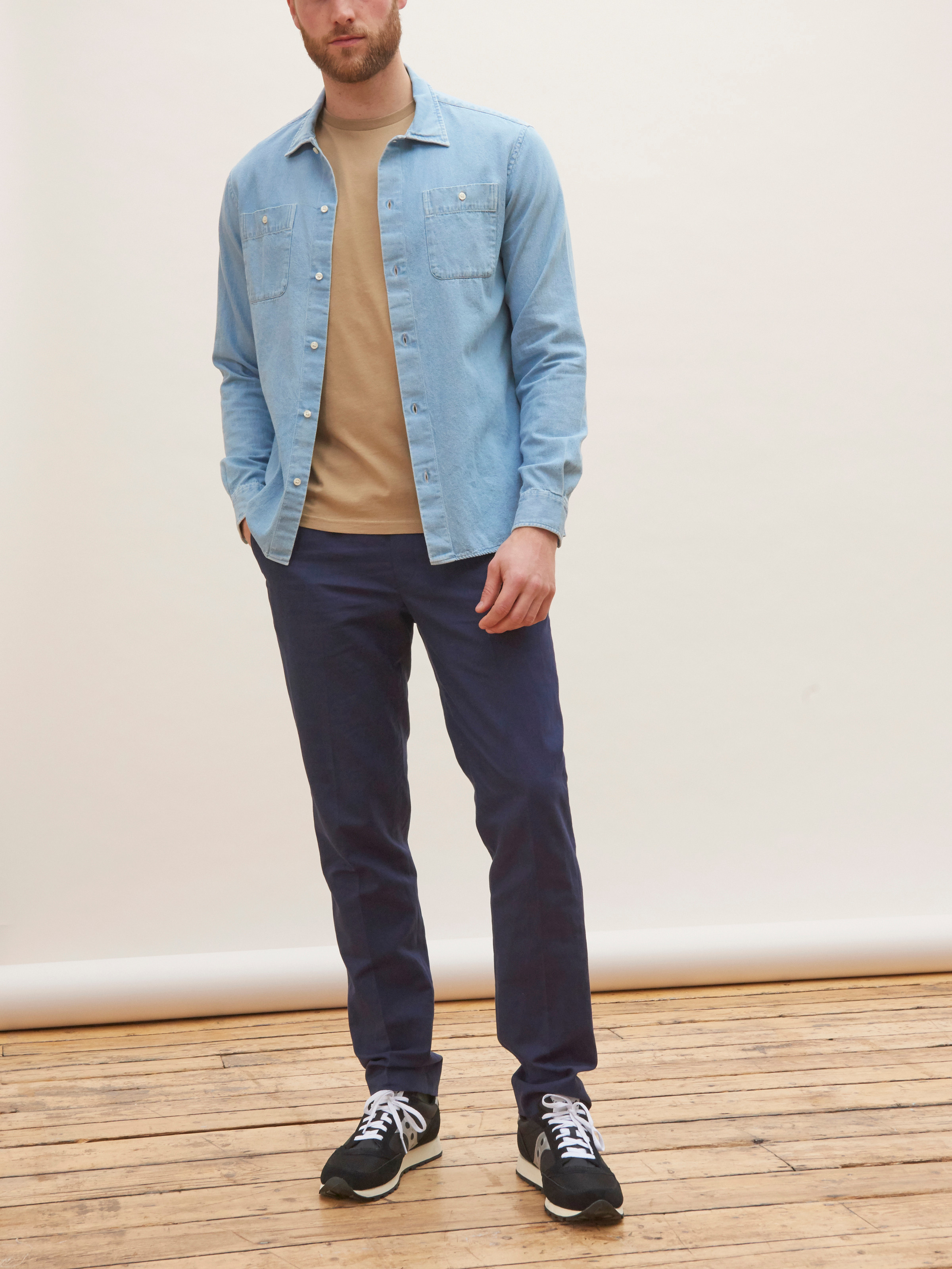 Men's outfit idea for 2021 with denim shirt, pale-colored crew neck t-shirt, navy dress pants, neutral sneakers. Suitable for spring and fall.