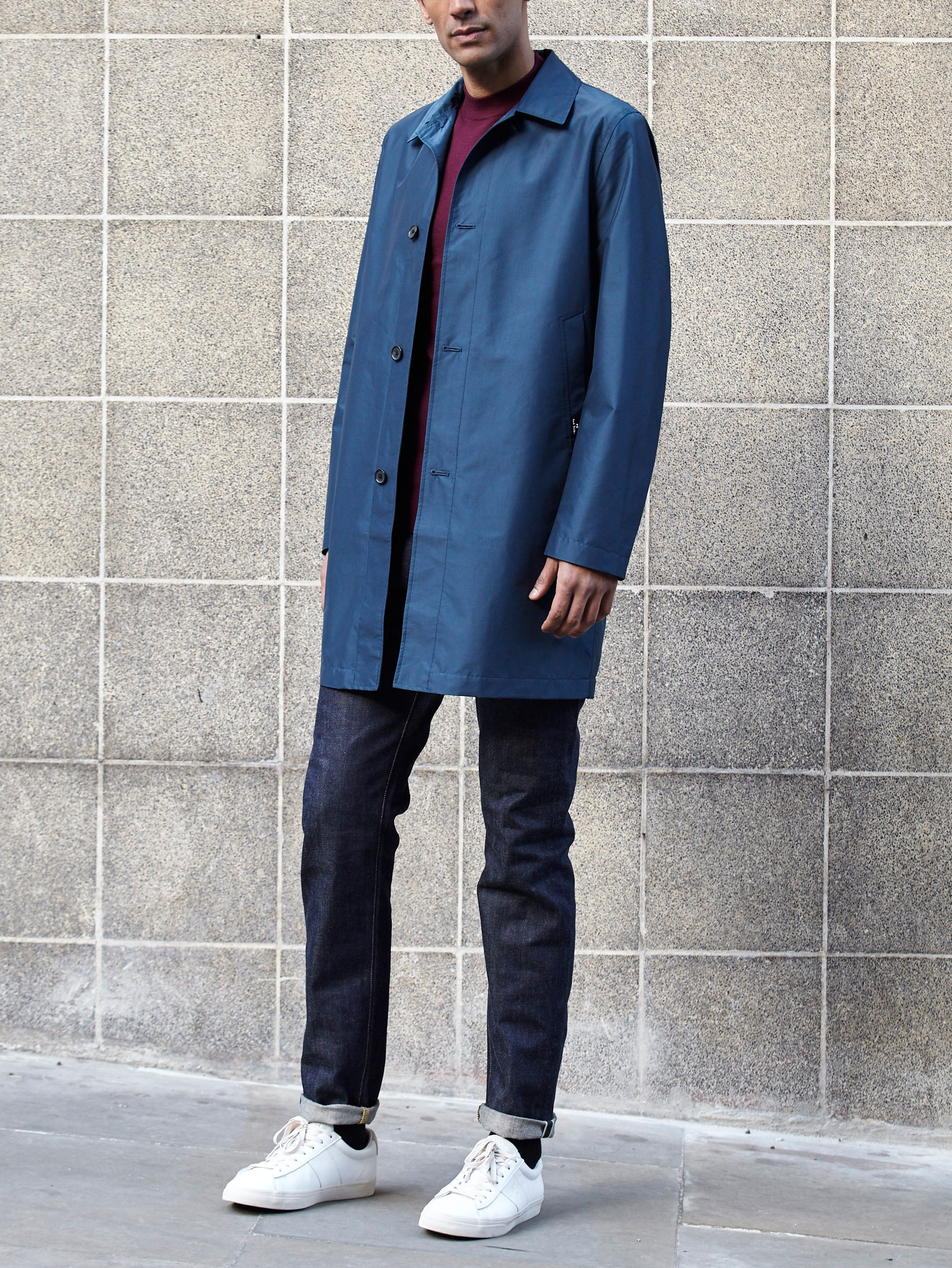 Men's outfit idea for 2021 with navy trench coat, bold coloured sweatshirt, dark blue jeans, white trainers. Suitable for spring and autumn.