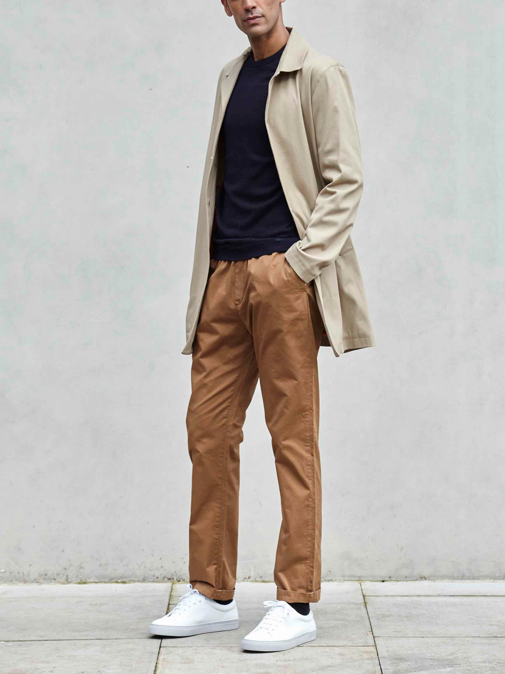 Men's outfit idea for 2021 with stone trench coat, navy crew neck knitted jumper, stone chinos, white trainers. Suitable for spring, autumn and winter.