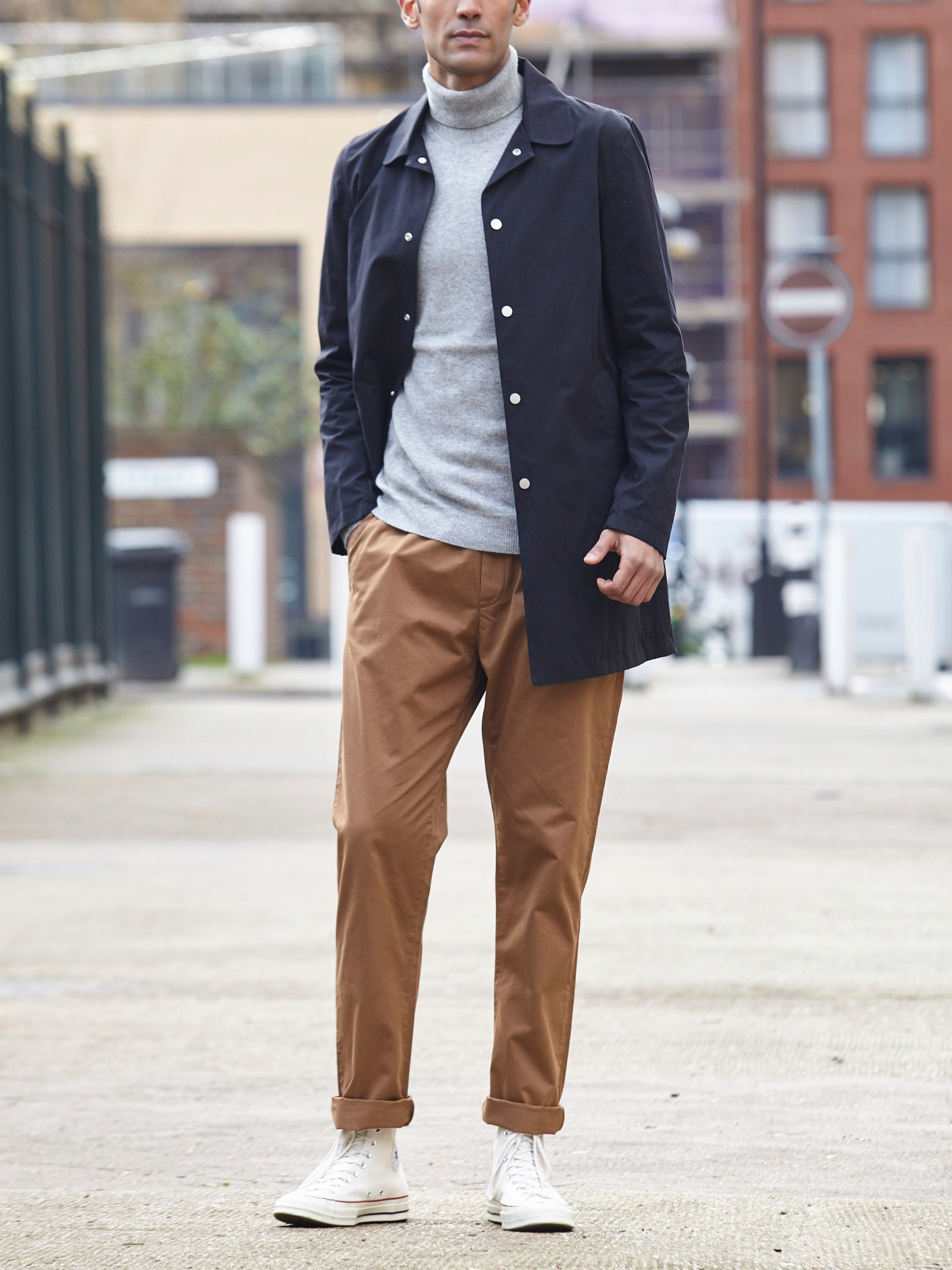 Men's outfit idea for 2021 with navy trench coat, grey lightweight rollneck jumper, stone chinos, converse. Suitable for spring, autumn and winter.
