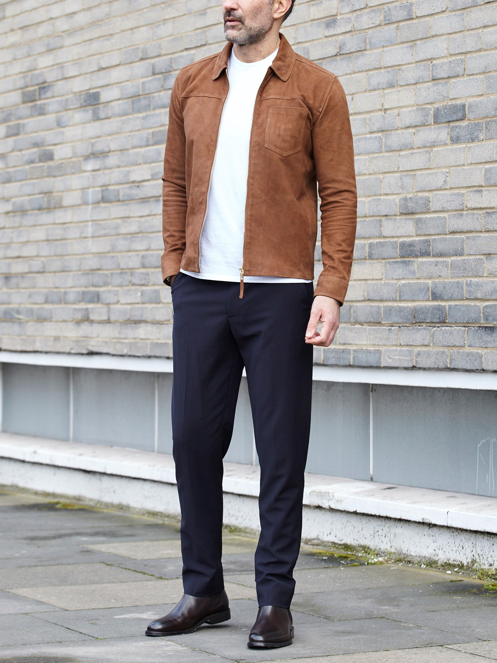 Men's outfit idea for 2021 with neutral utility jacket, white crew neck t-shirt, navy formal trousers, brown chelsea boots. Suitable for spring and autumn.