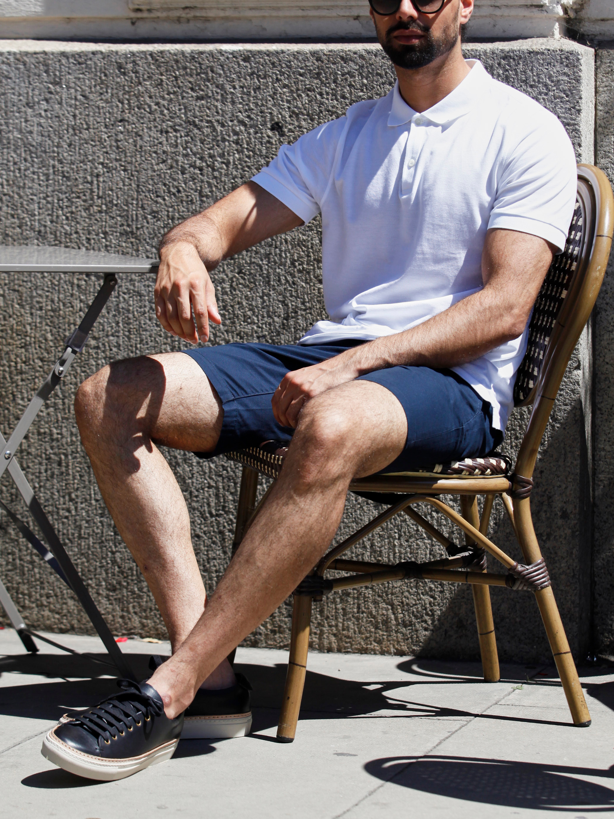 Men's outfit idea for 2021 with white polo, navy shorts, black sunglasses, black trainers. Suitable for summer.