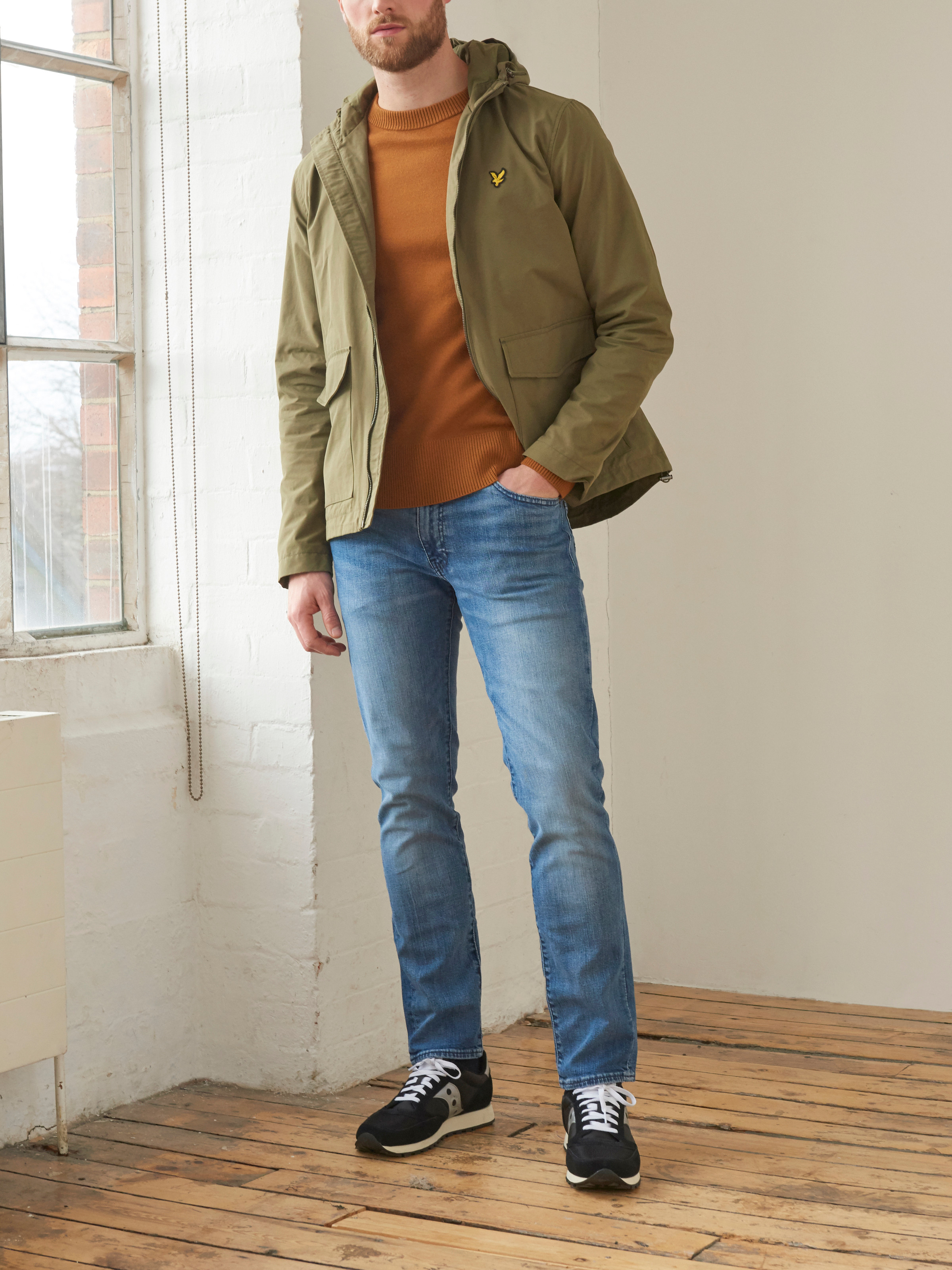 Men's outfit idea for 2021 with waterproof jacket / windbreaker, bold coloured sweatshirt, mid blue jeans, neutral trainers. Suitable for spring, autumn and winter.