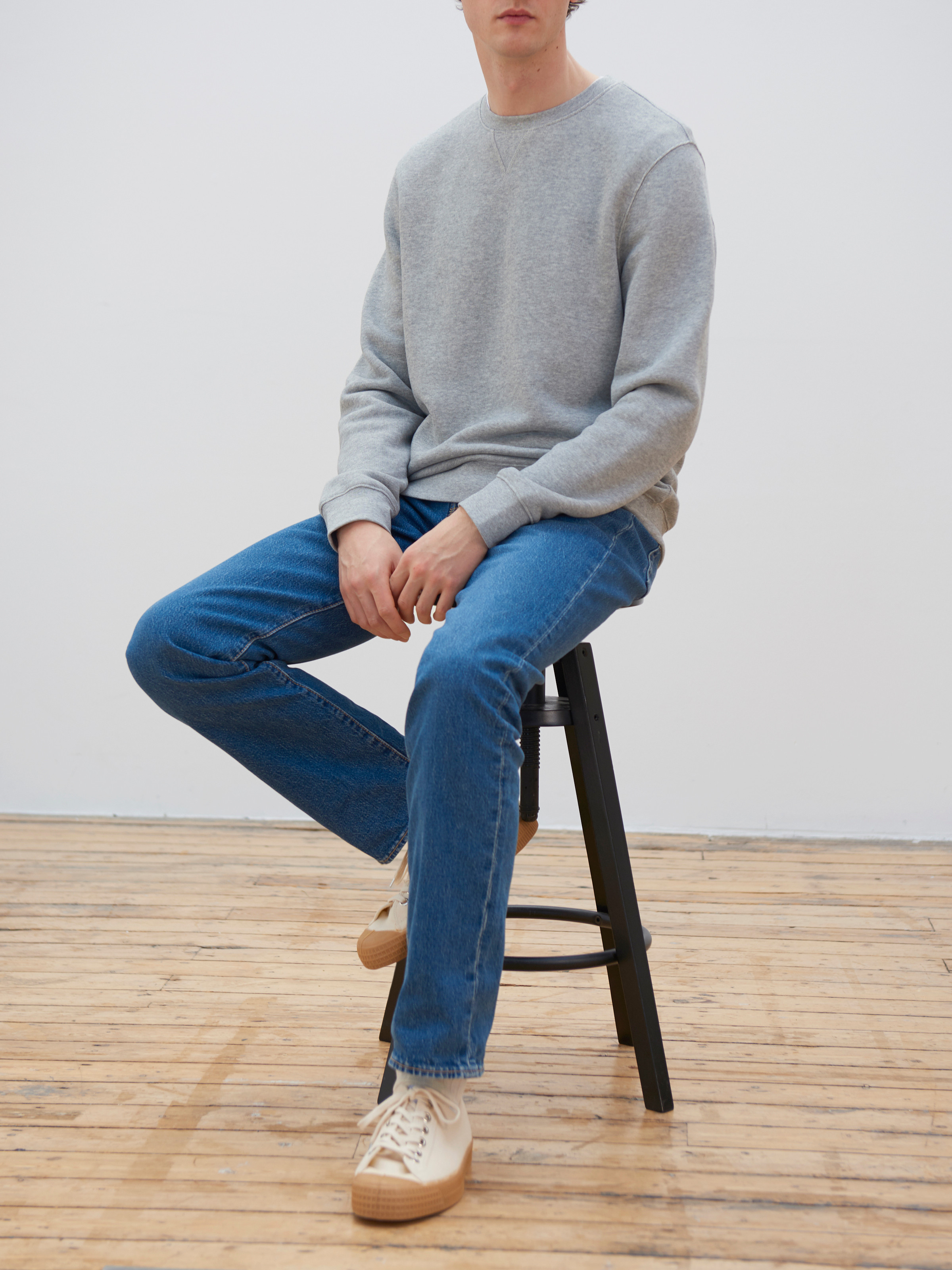 Men's outfit idea for 2021 with grey sweatshirt, mid blue jeans, white trainers. Suitable for spring, summer and autumn.
