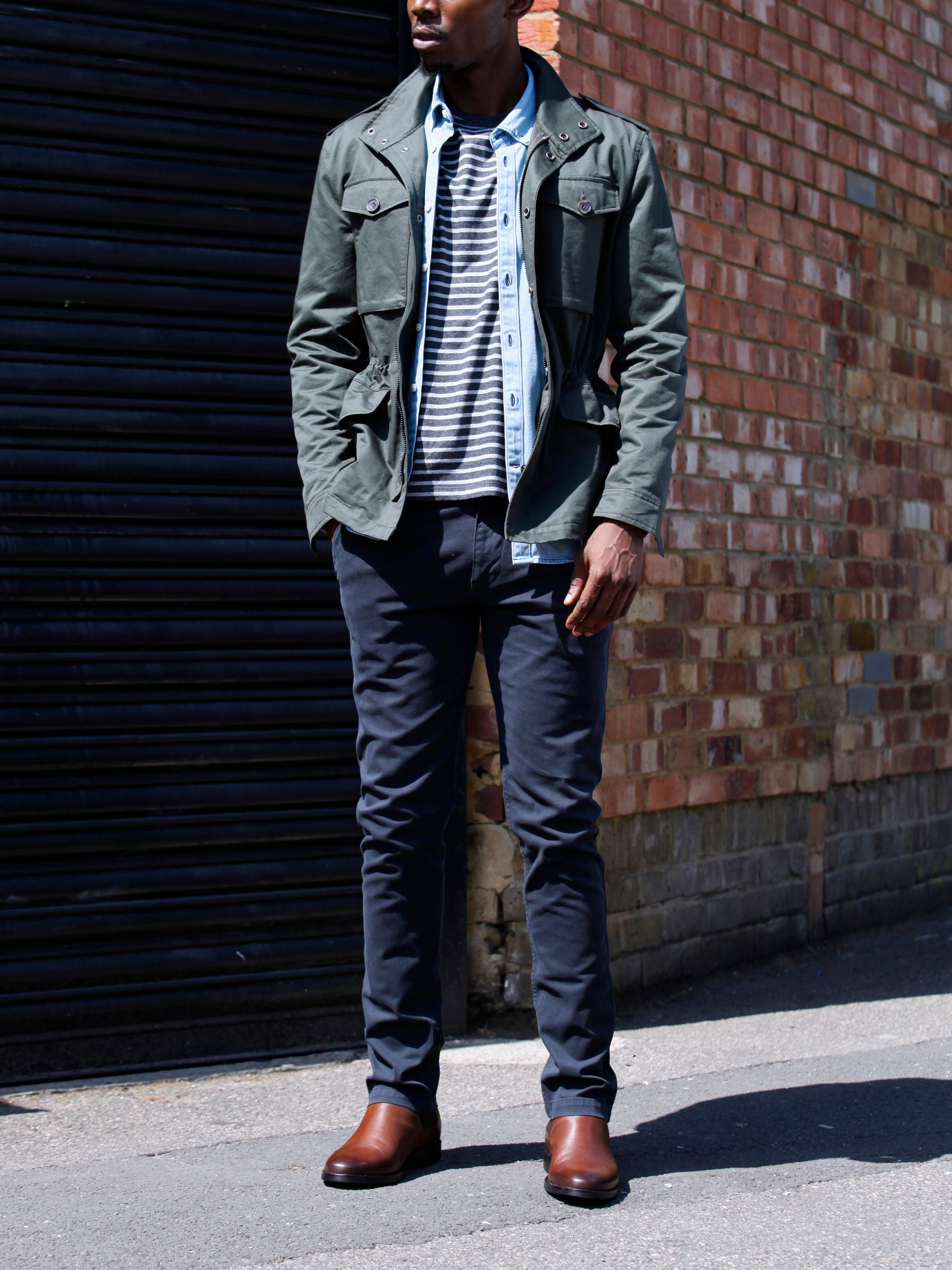 Men's outfit idea for 2021 with field jacket, denim shirt, striped crew neck t-shirt, navy chinos, brown chelsea boots. Suitable for spring and fall.