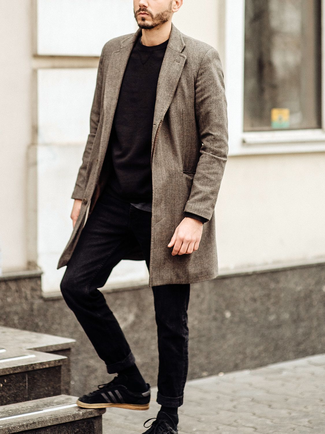 Men's outfit idea for 2021 with brown single-breasted overcoat, black sweatshirt, black jeans, black trainers / sneakers. Suitable for autumn and winter.