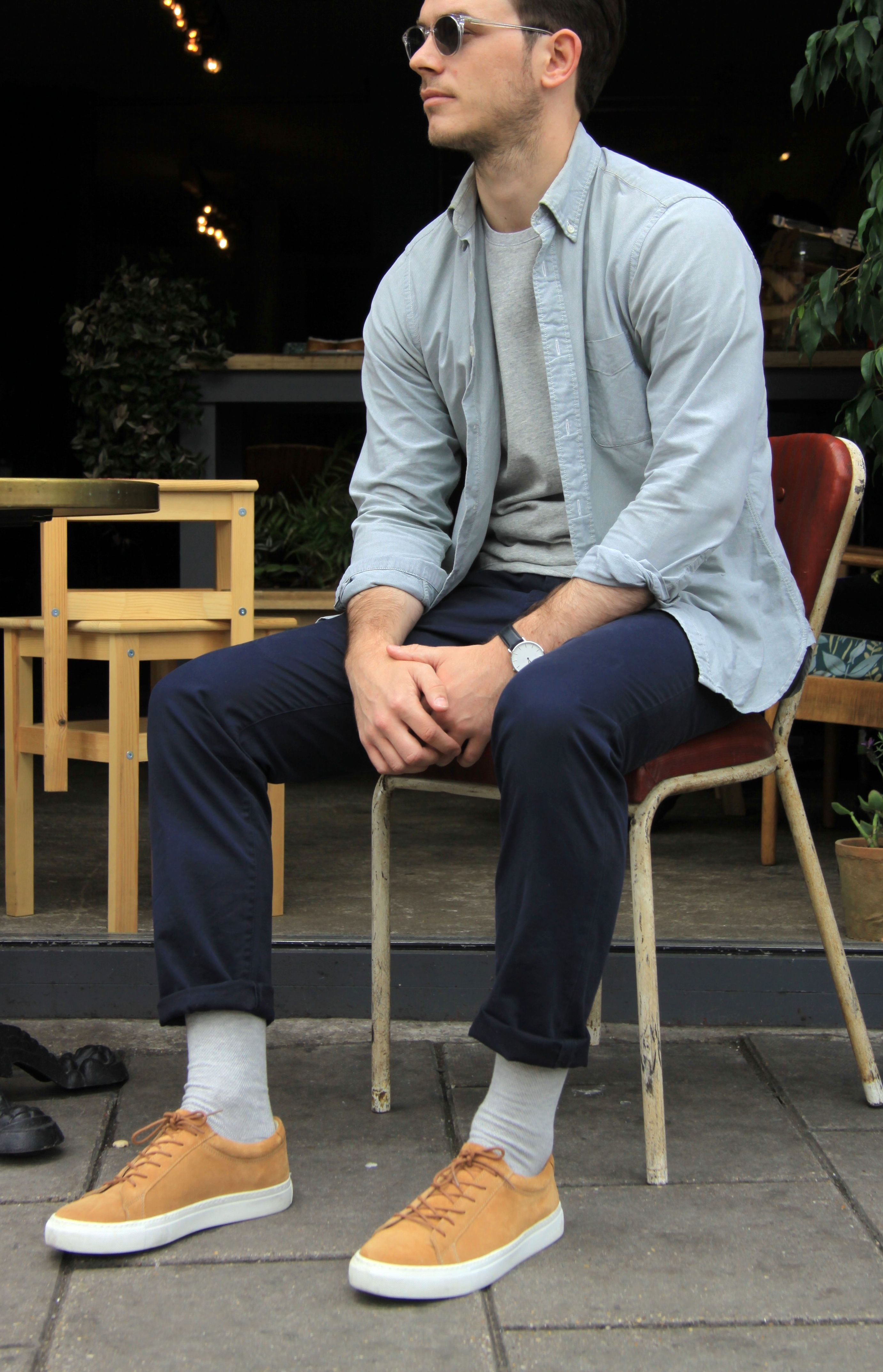 Men's outfit idea for 2021 with chambray shirt, gray crew neck t-shirt, navy chinos, neutral sneakers. Suitable for spring, summer and fall.