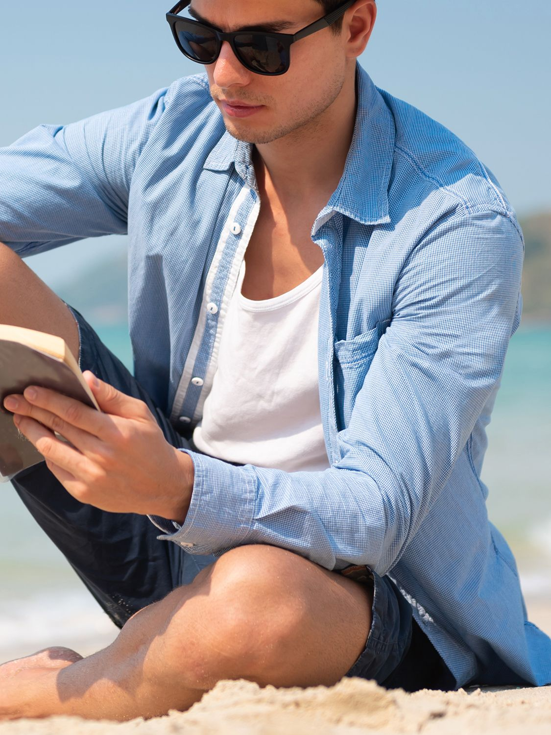 Men's outfit idea for 2021 with blue micro plaid casual shirt, white plain tank top, navy cotton shorts, black sandals. Suitable for spring and summer.