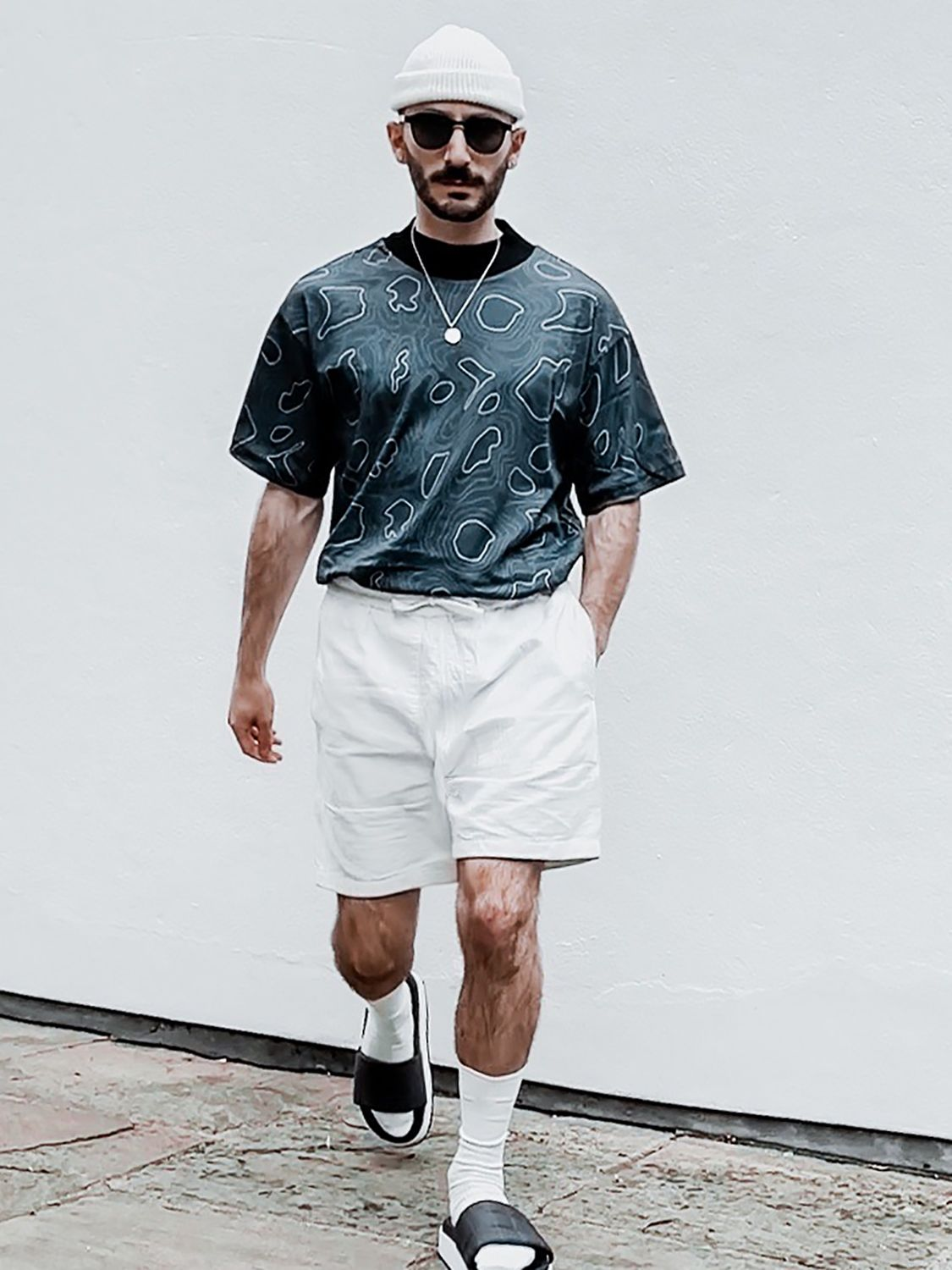 Men's outfit idea for 2021 with black patterned crew neck t-shirt, white sweat shorts, black flipflops. Suitable for summer.
