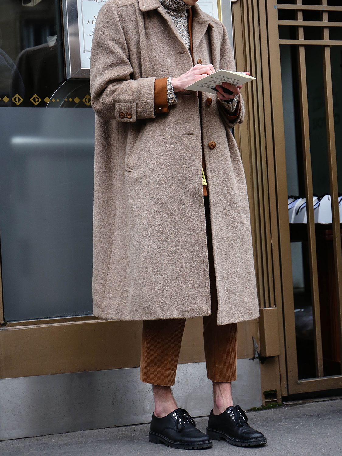 Men's outfit idea for 2021 with neutral camel coat, utility jacket, neutral lightweight rollneck jumper, black oxford / derby shoes. Suitable for winter.