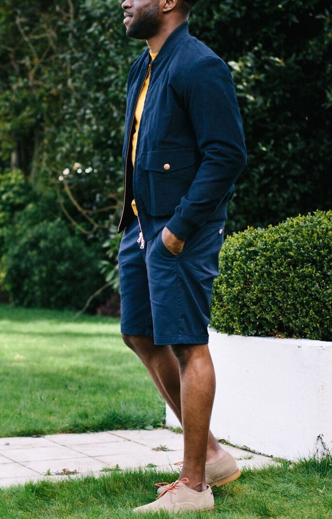 Men's outfit idea for 2021 with bomber jacket, bold coloured long-sleeved t-shirt, navy shorts, suede shoes / desert shoes. Suitable for summer.