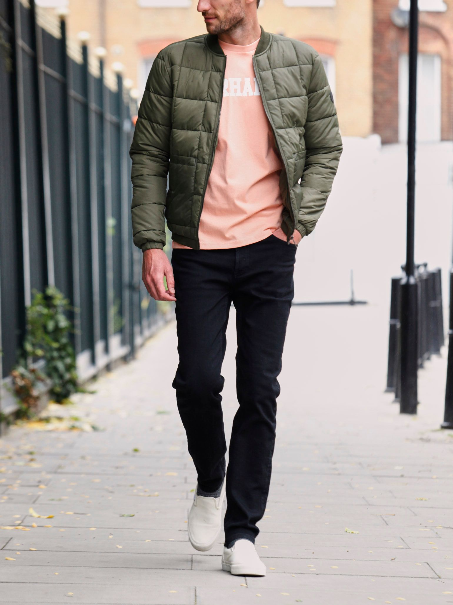 Men's outfit idea for 2021 with bomber jacket, logo printed crew neck t-shirt, black jeans, plimsolls. Suitable for spring and fall.
