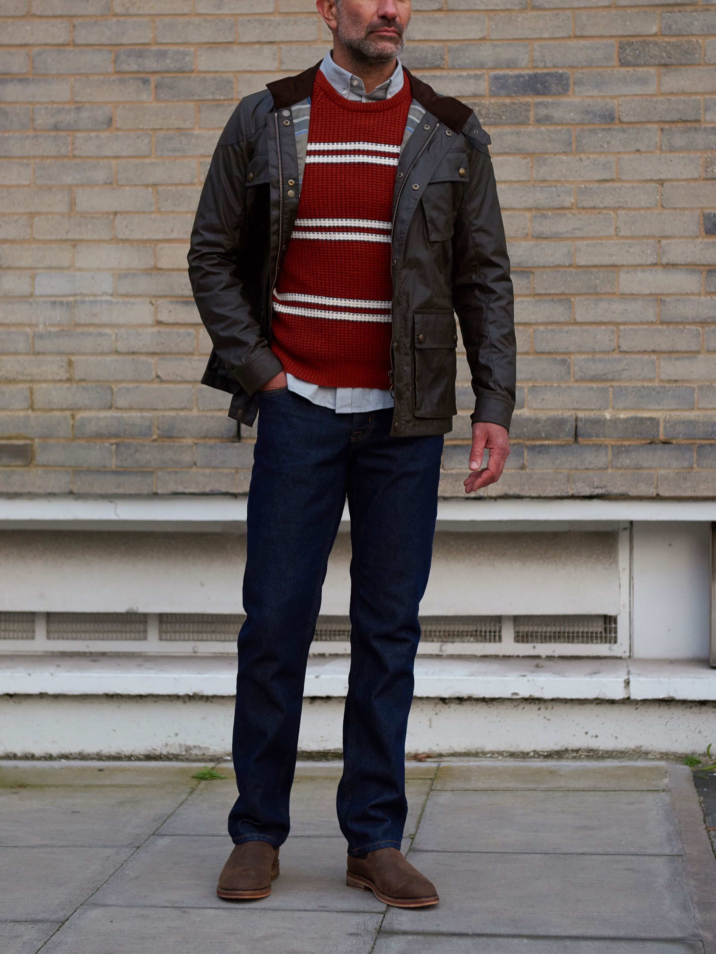 Men's outfit idea for 2021 with red plain crew neck knitted jumper, pale coloured casual shirt, dark blue jeans, brown chelsea boots. Suitable for autumn and winter.