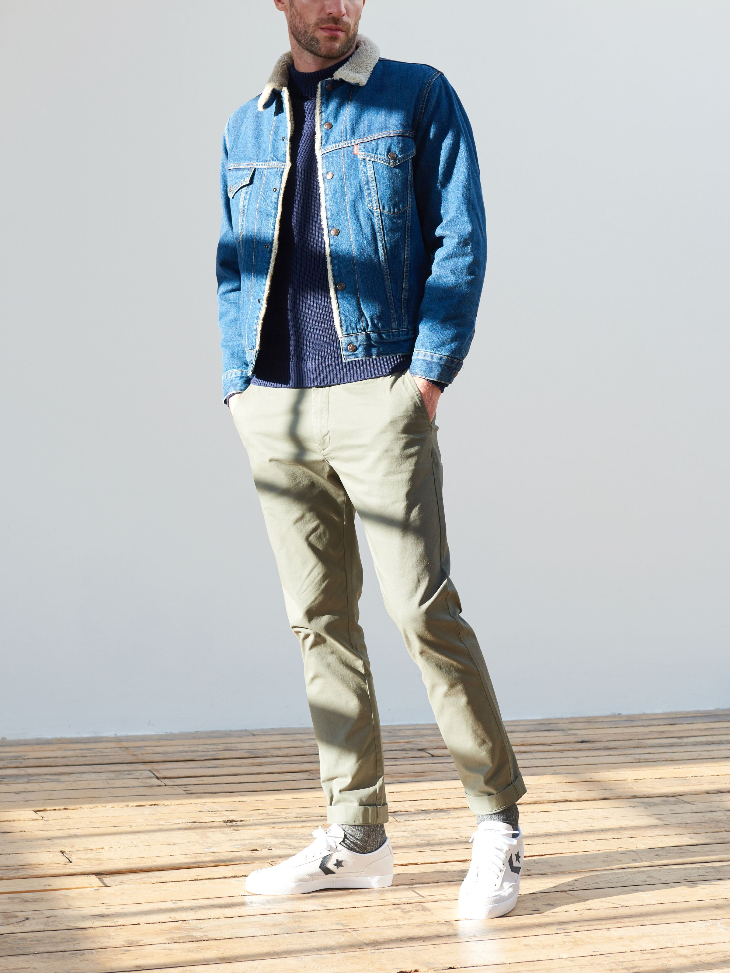 Men's outfit idea for 2021 with dark denim jacket, navy crew neck knitted sweater, colored chinos, converse. Suitable for spring and fall.