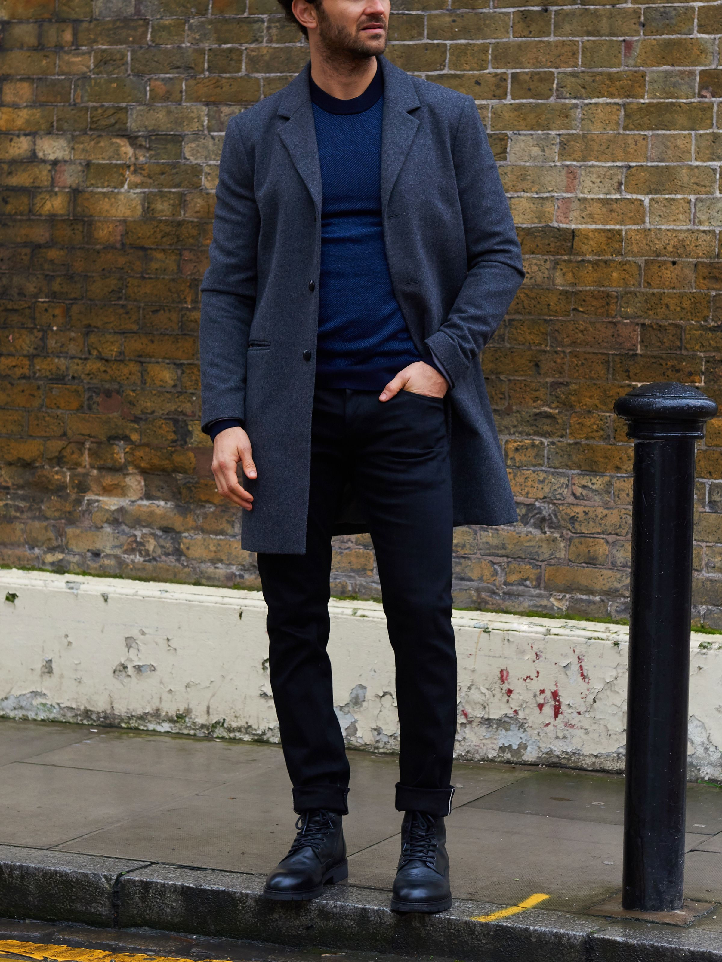 Men's outfit idea for 2021 with single-breasted overcoat, navy plain crew neck knitted jumper, black jeans, lace-up leather boots. Suitable for autumn and winter.