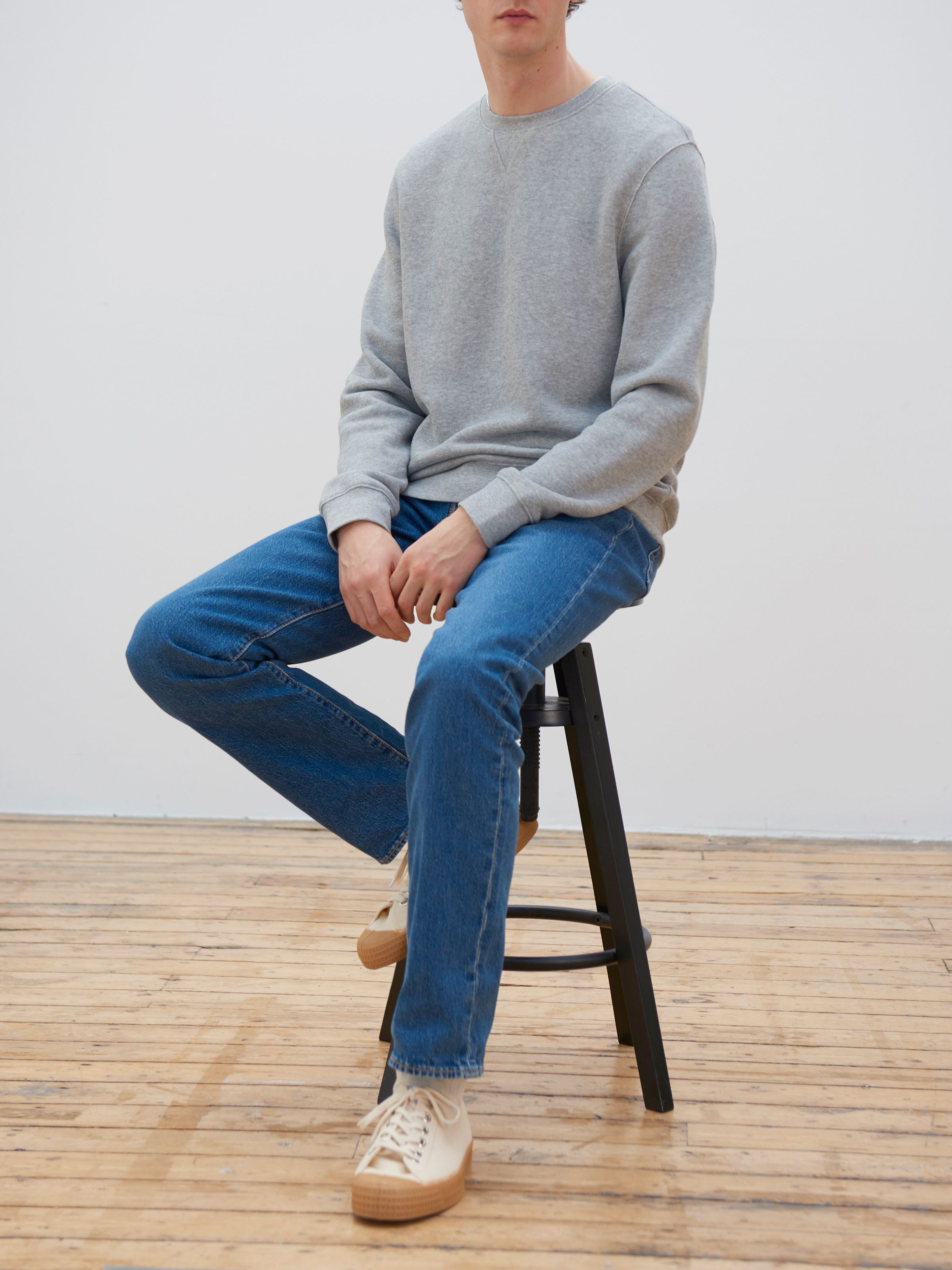 Men's outfit idea for 2021 with gray sweatshirt, mid blue jeans, white sneakers. Suitable for spring, summer and fall.