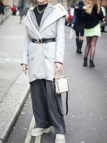 Women's outfit idea for 2021 with grey overcoat, grey blazer, black top, grey casual trousers, white trainers. Suitable for fall and winter.