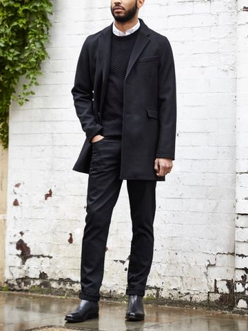 Men's outfit idea for 2021 with single-breasted overcoat, black crew neck knitted jumper, white casual shirt, black jeans, black chelsea boots. Suitable for spring, autumn and winter.