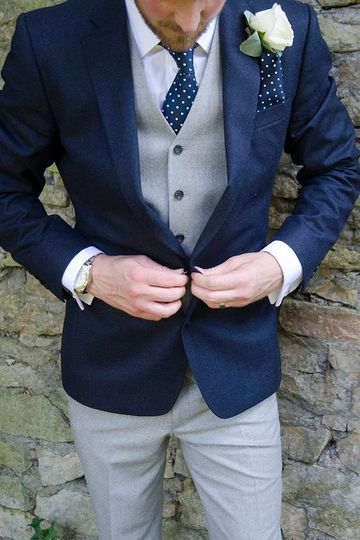Men's outfit idea for 2021 with navy blazer, white formal shirt, grey plain waistcoat, patterned tie, grey formal trousers. Suitable for spring, summer and autumn.