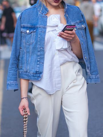 Women's outfit idea for 2021 with blue denim jacket, white shirt, white smart trousers, white trainers. Suitable for spring, summer and autumn.