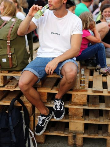 Men's outfit idea for 2021 with logo printed crew neck t-shirt, denim shorts, rucksack, black trainers. Suitable for summer.