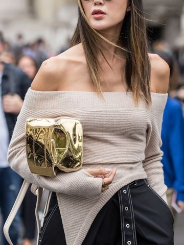 Women's outfit idea for 2021 with neutral jumper, black casual trousers, metallic clutch bag, white trainers. Suitable for spring, summer and autumn.