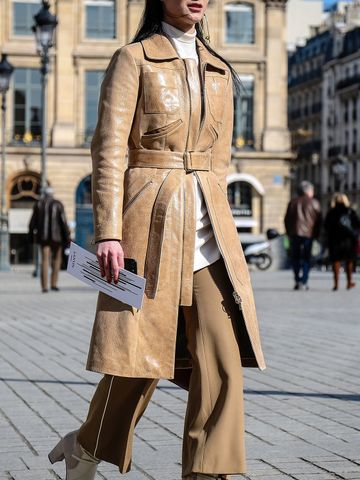 Women's outfit idea for 2021 with neutral trench coat, neutral jumper, white clutch bag, white ankle boots. Suitable for autumn and winter.