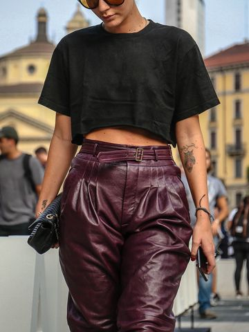 Women's outfit idea for 2021 with black tshirt, red casual trousers, black cross body bag, black ankle boots. Suitable for spring and summer.